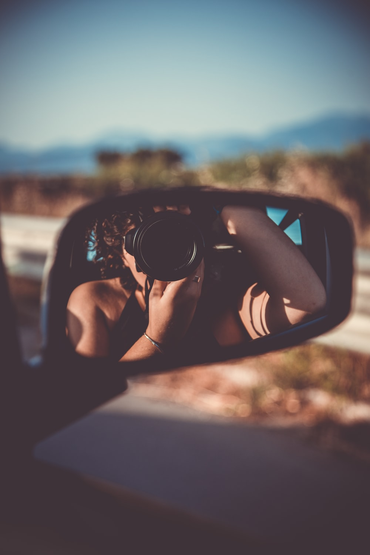 person taking selfie through vehicle wing mirror