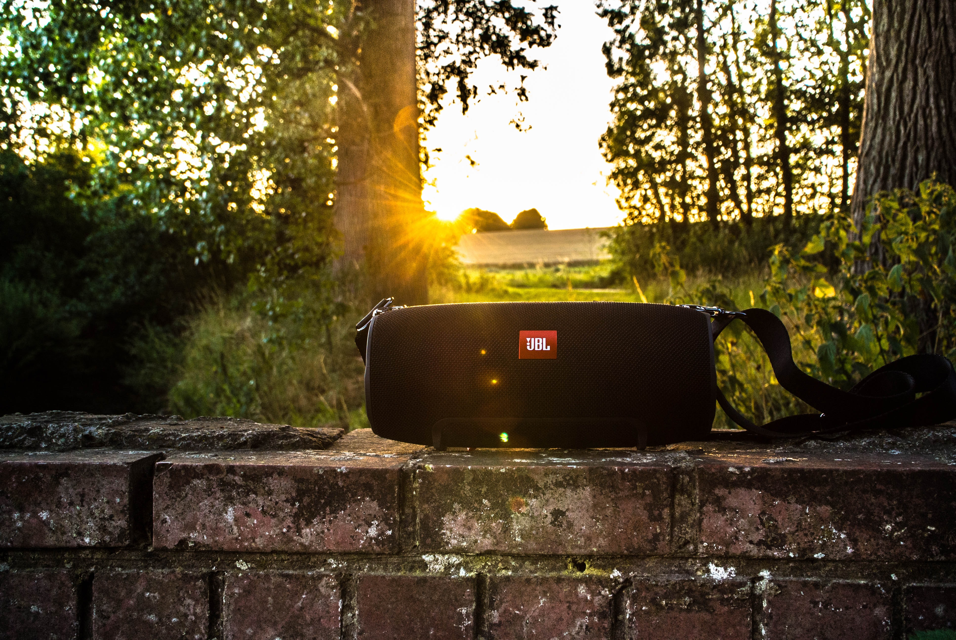 black JBL portable speaker on brick bench
