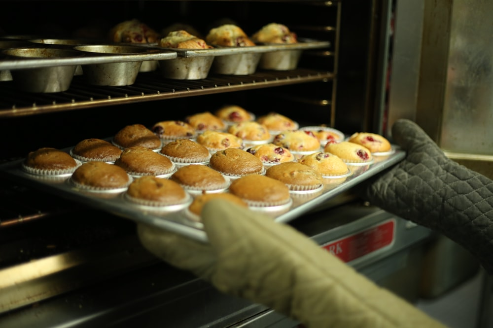 A person with oven mitts is loading the oven with a tray of muffins