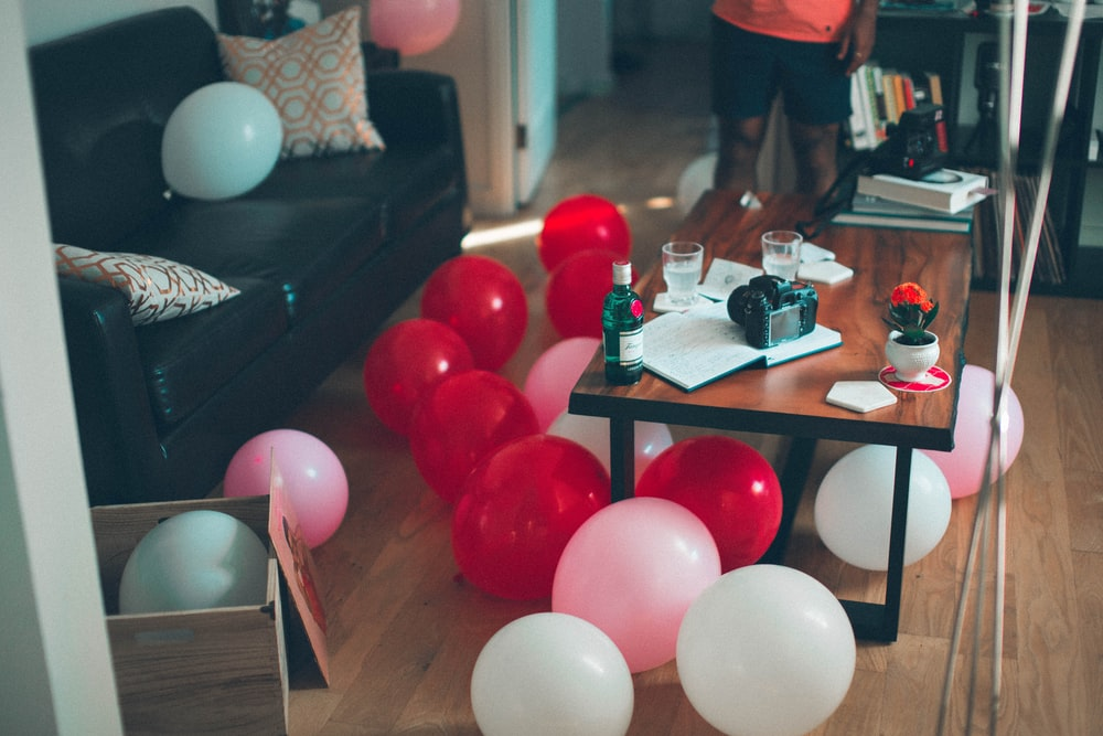 Red, pink and white balloons on the floor in a living room in Toronto, ahead of a house party
