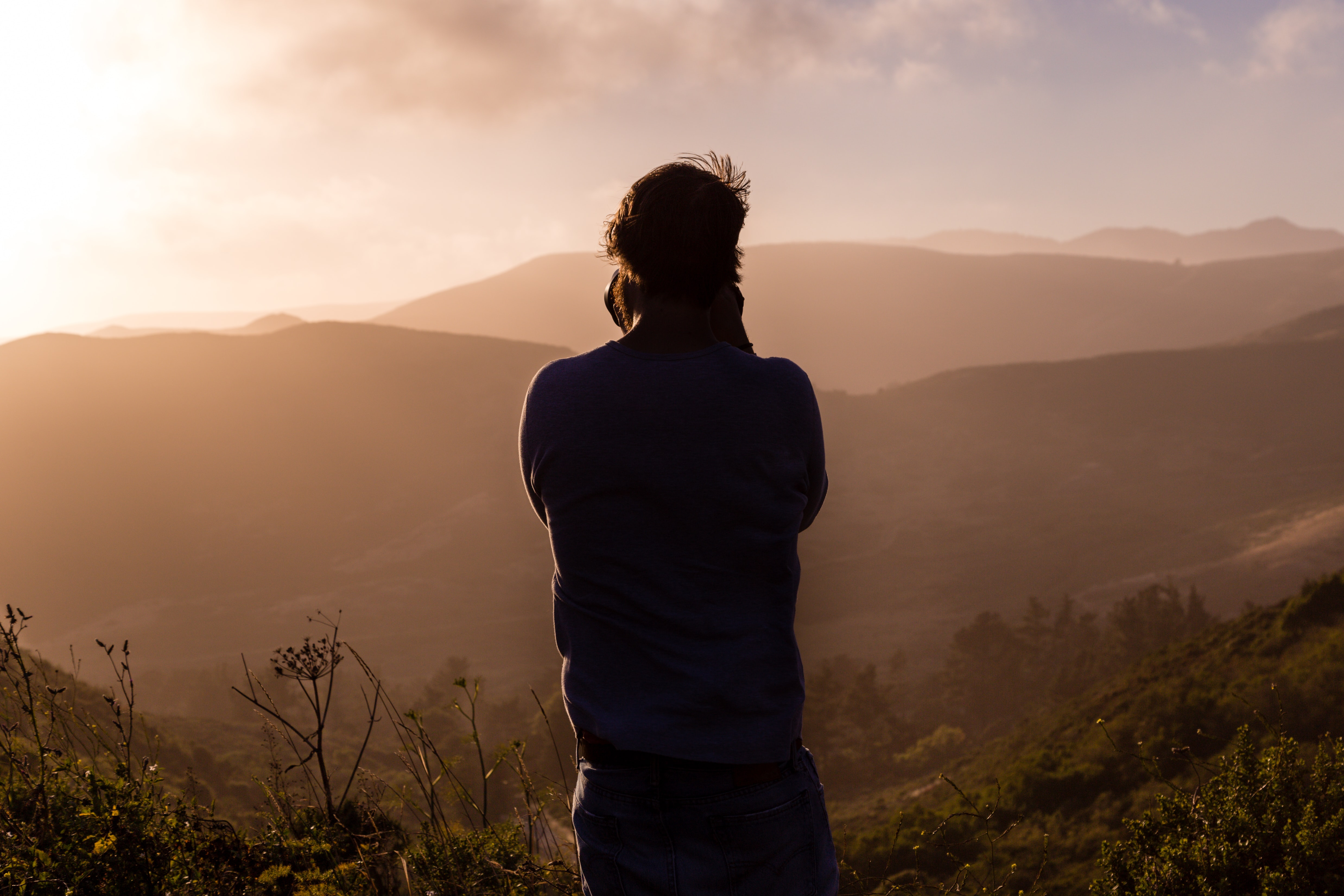 Silhouette of a photographer taking a picture of a sunset over mountains