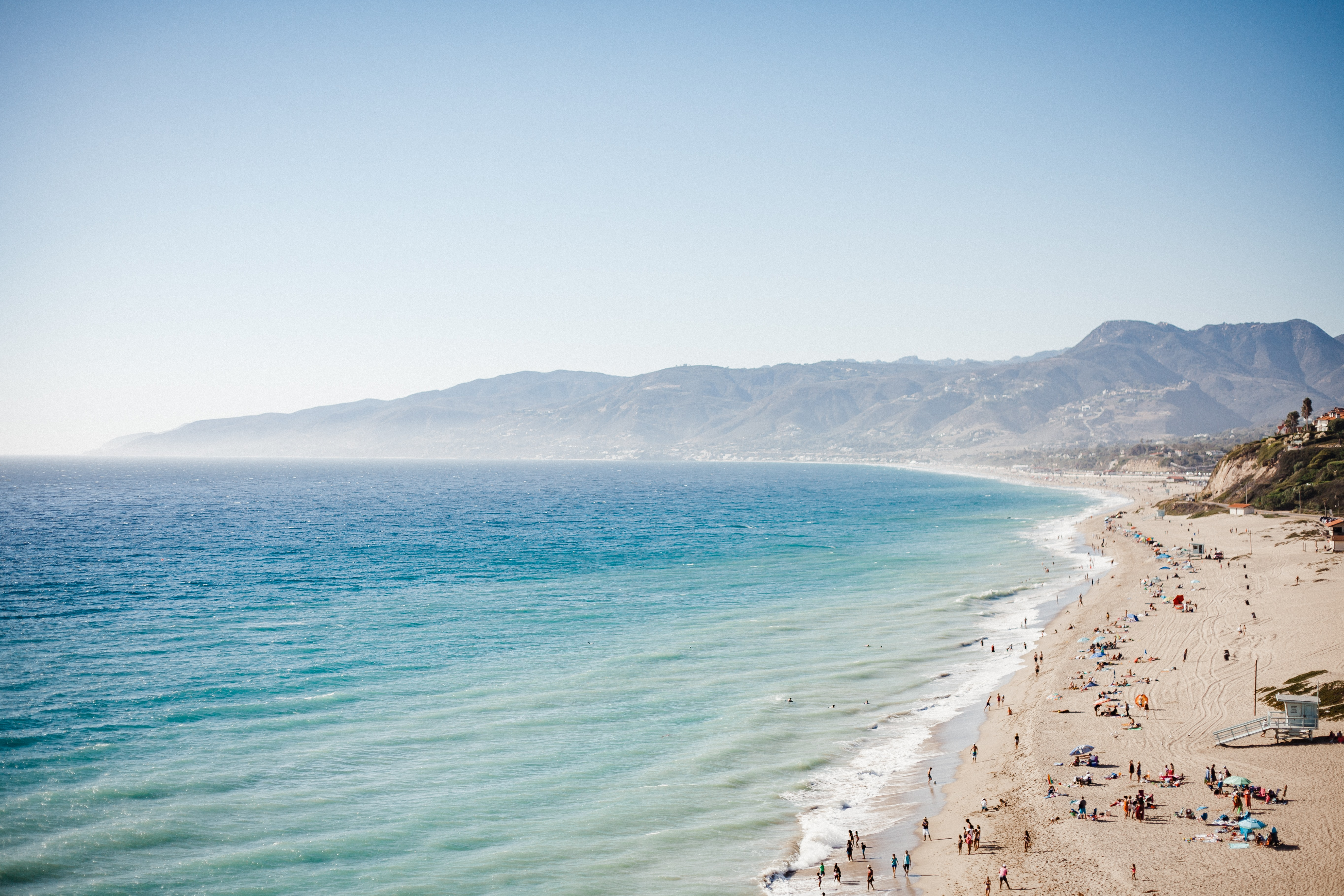 Clean ocean washing up on sand shore filled with people in Malibu