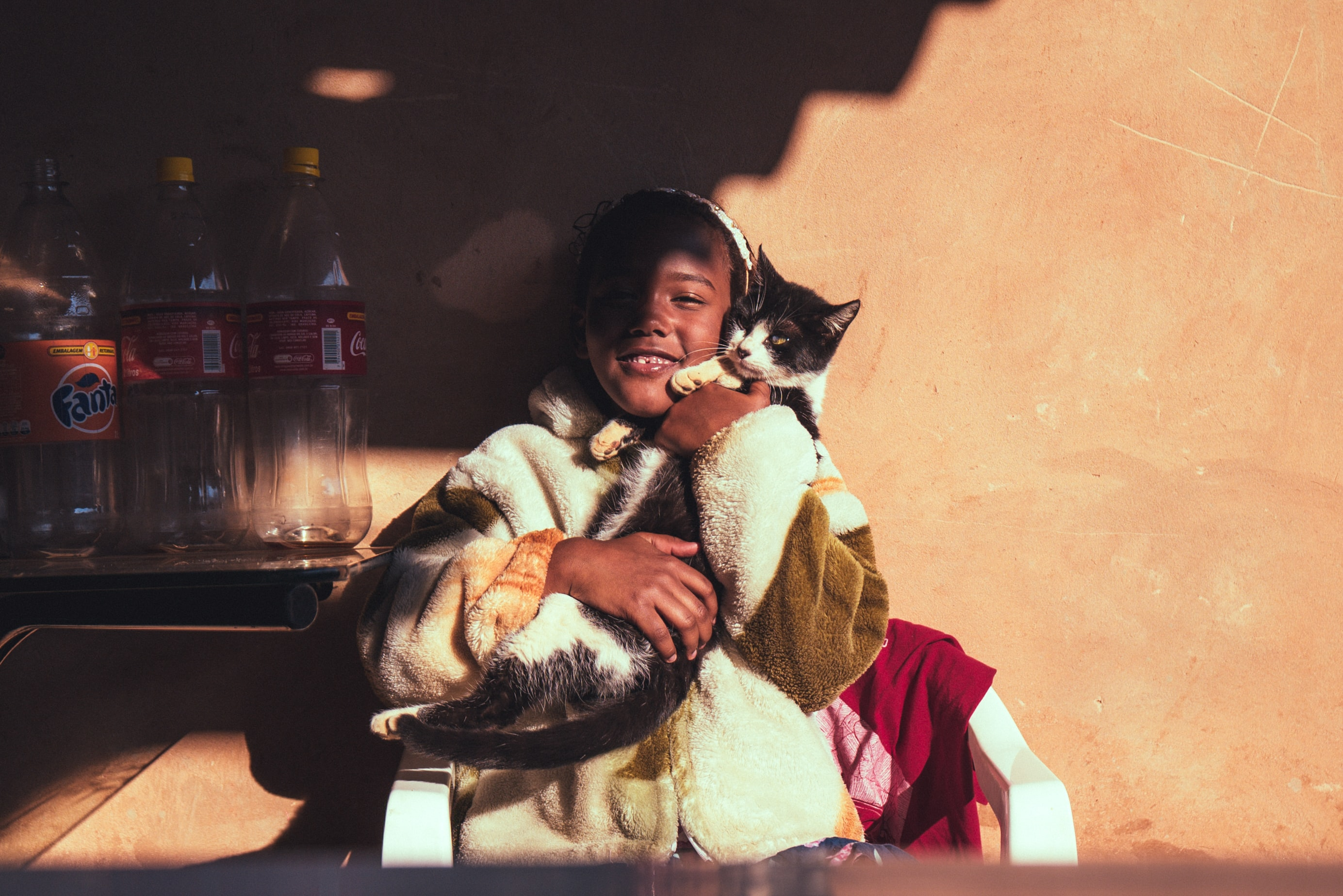 A shadow falls on a seated young girl smiling and cuddling a black and white cat
