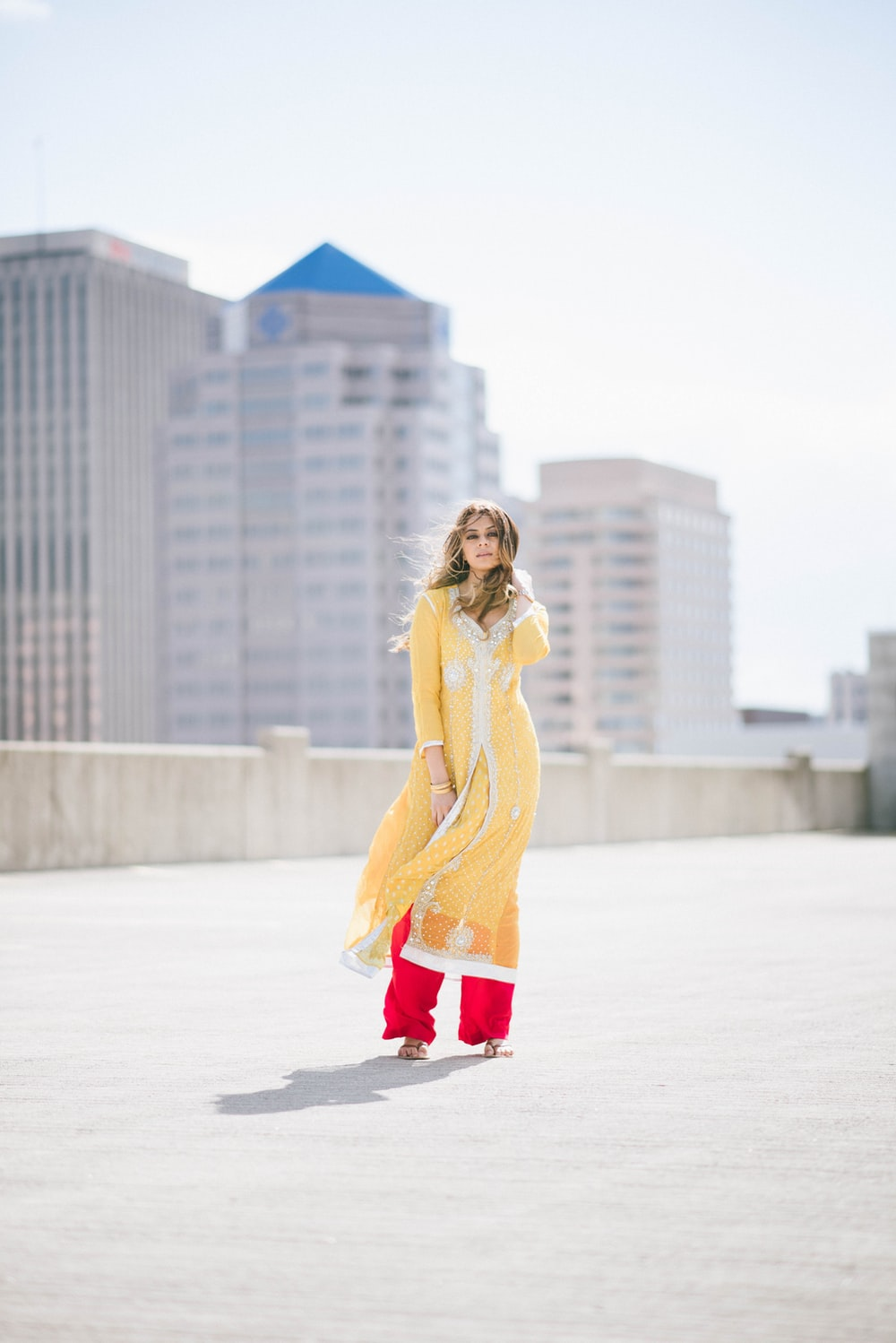 woman in yellow shalwar kameez standing on concrete floor holding her hair during daytime