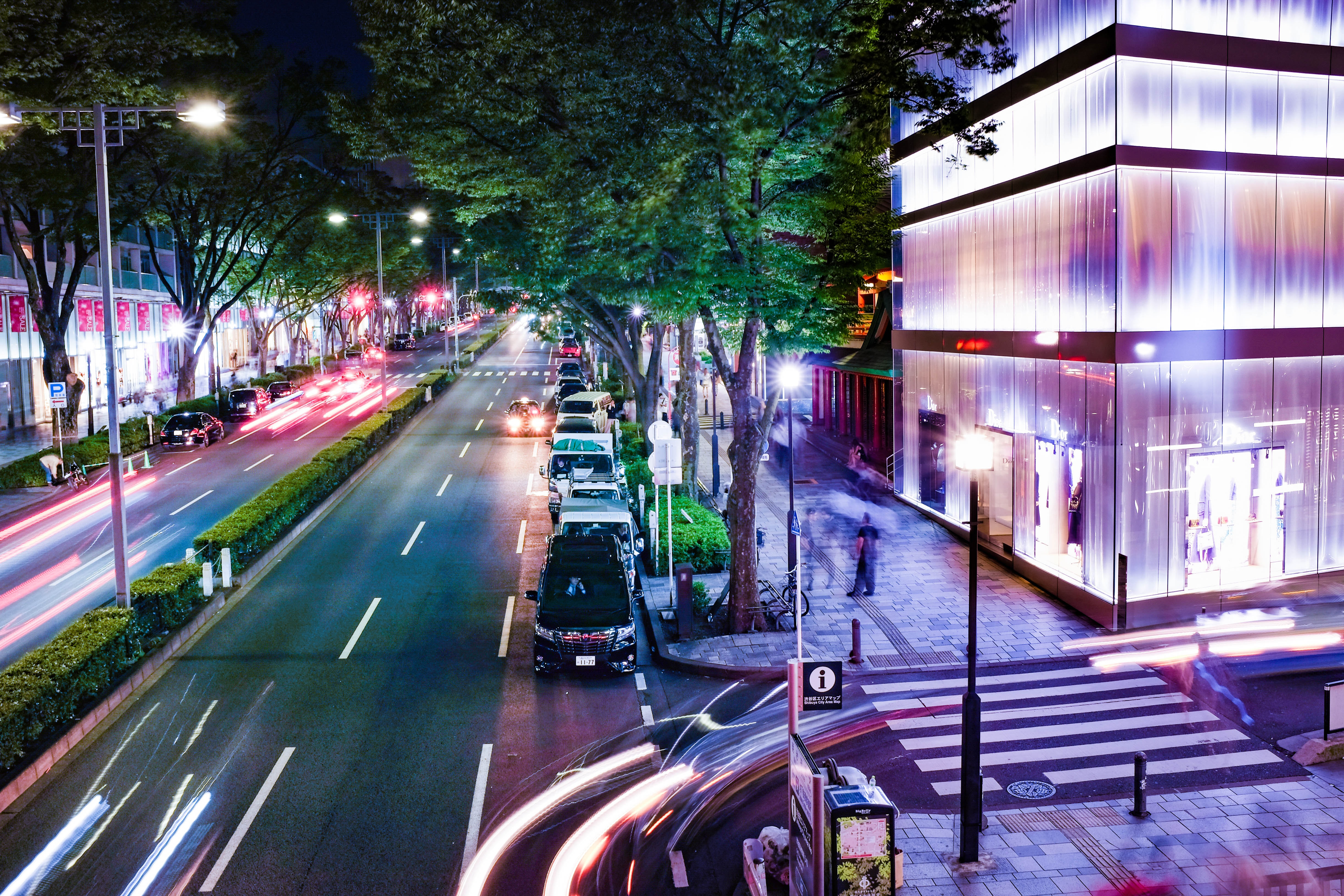 Long exposure photo of an avenue with people, cars and a facade lit building at night at the Omote-sando Station