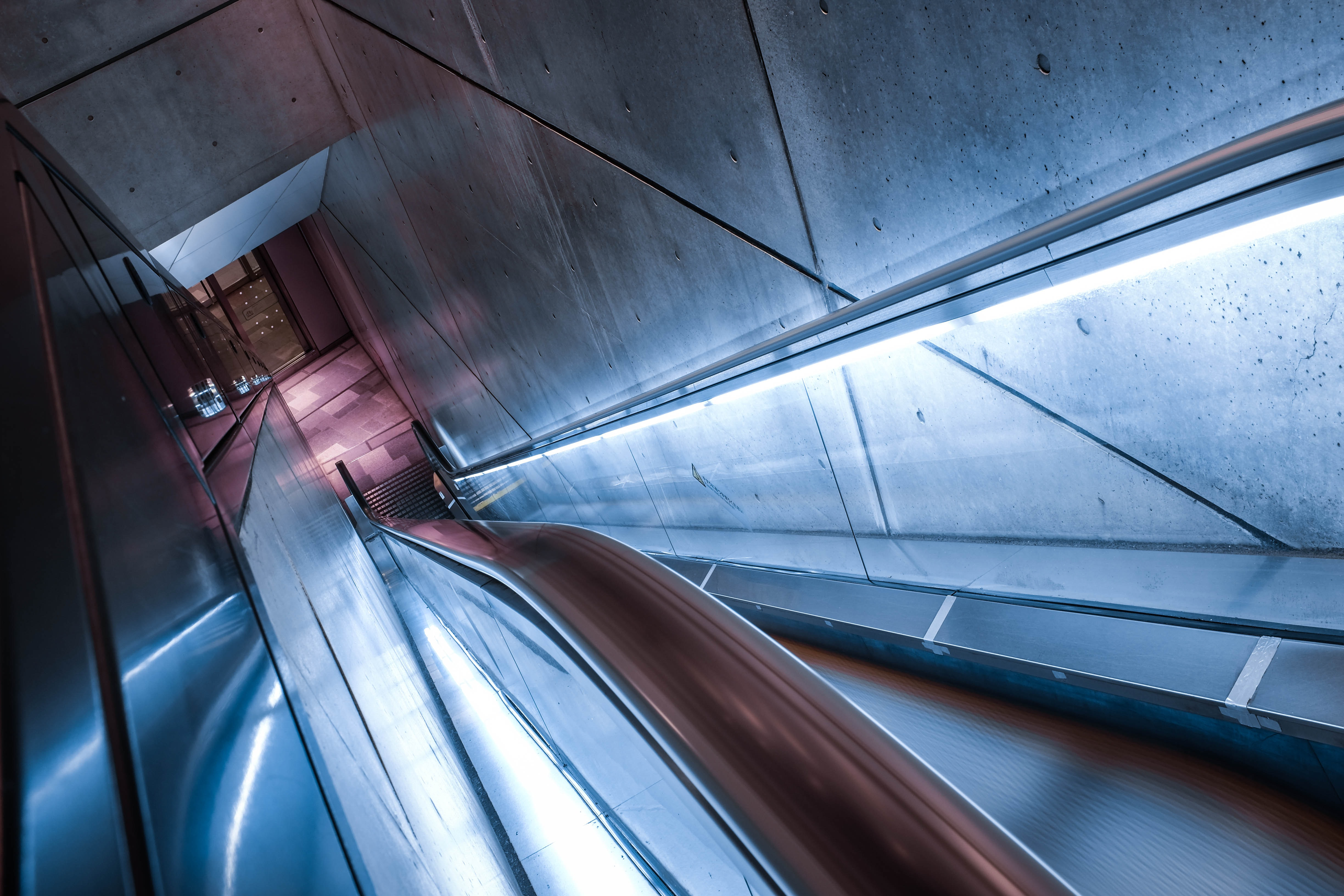 Looking down at an urban escalator enclosed in a concrete tunnel at Omotesando Hills