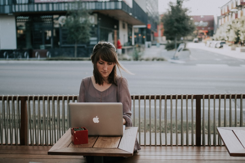 A woman working on a laptop outside a coffee store