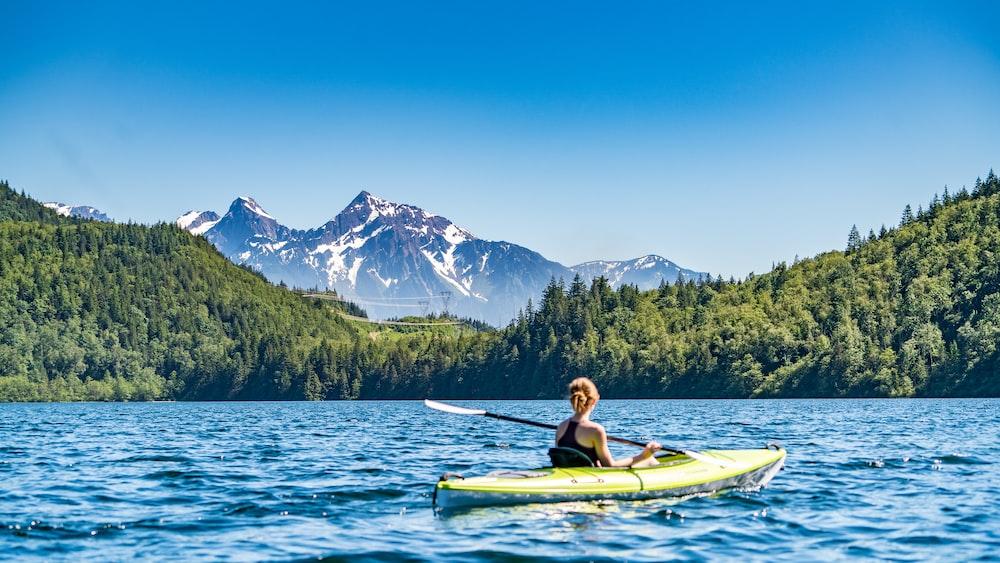 woman kayaking on lake during daytime