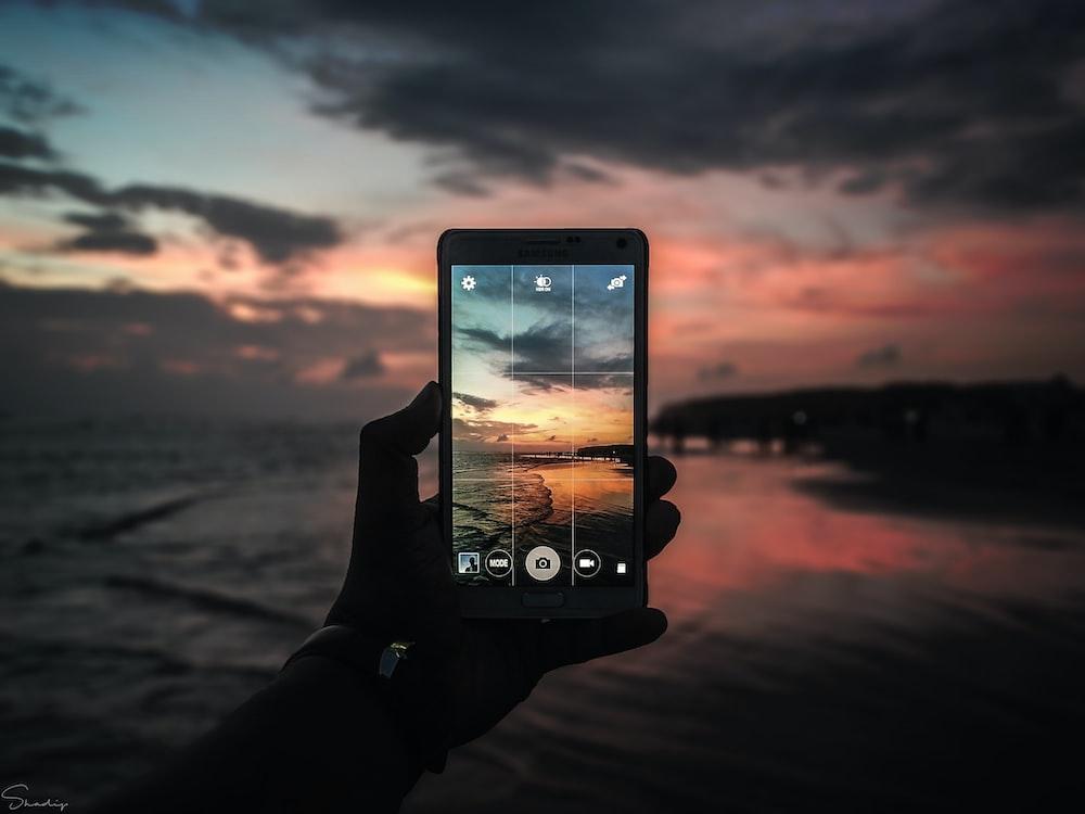 black smartphone taking photo of golden hour horizon
