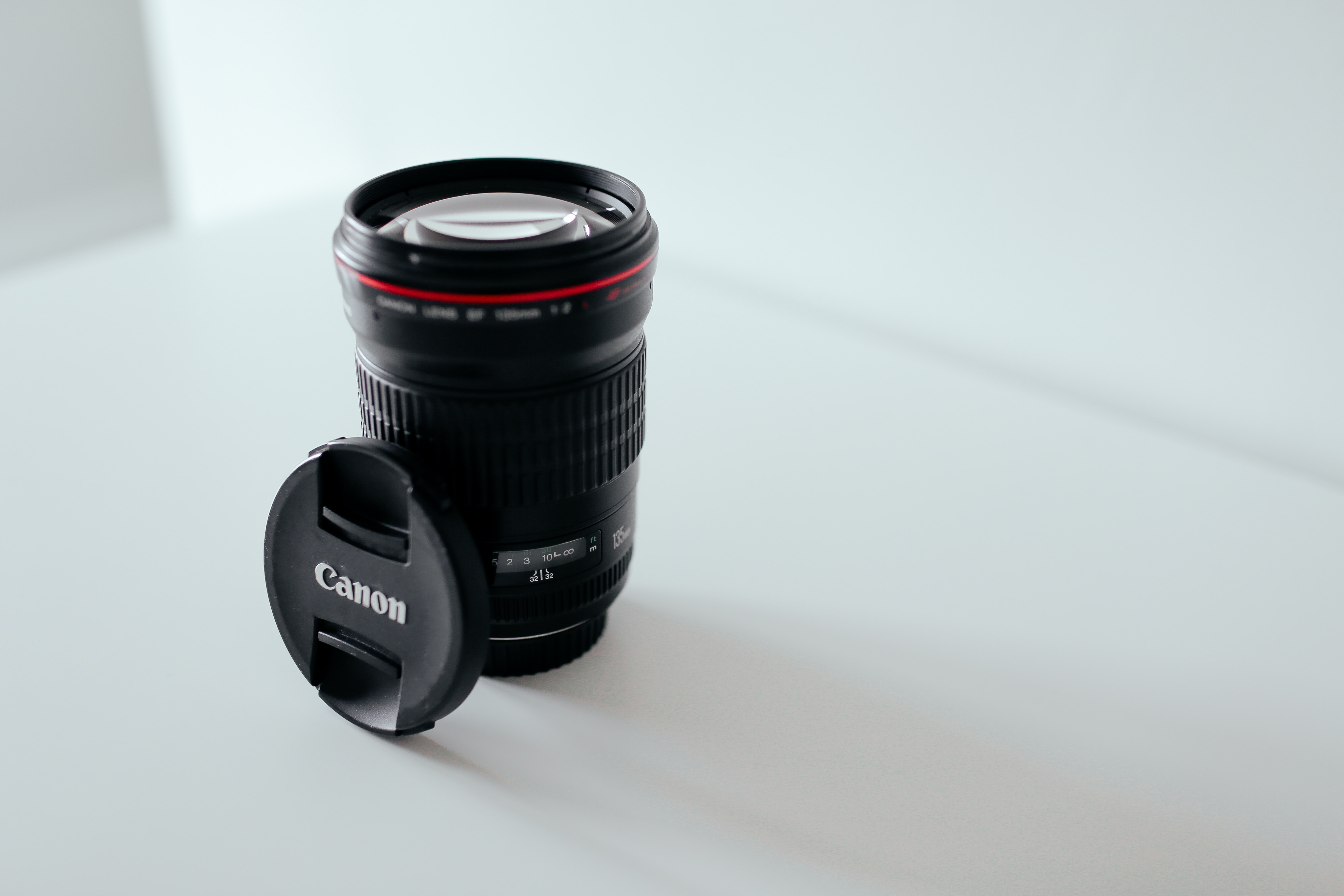 Canon camera lens with cover balancing on its side in a white room