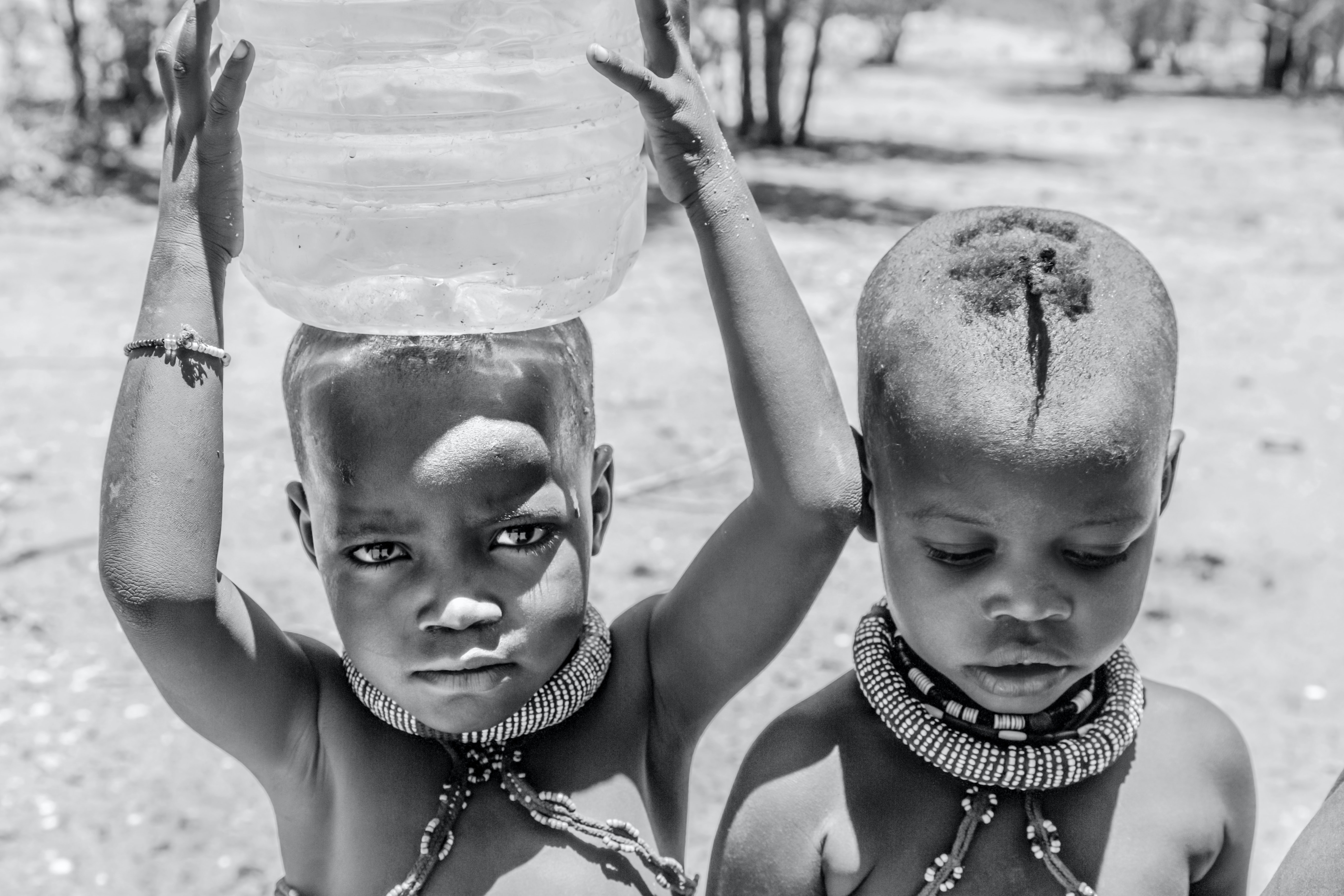 Young children in necklaces hold water over head in Namibia