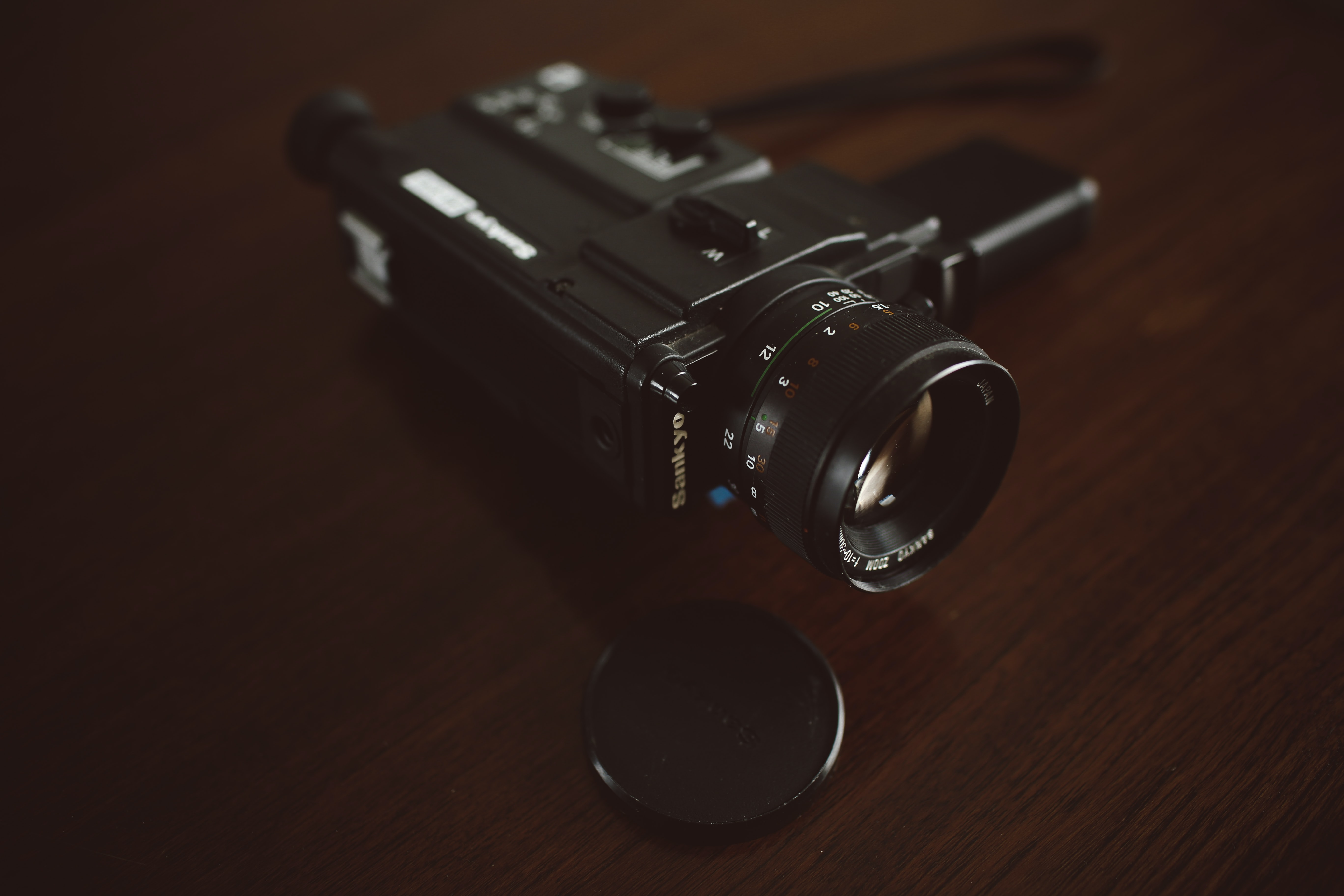 black video camera on brown wooden surface