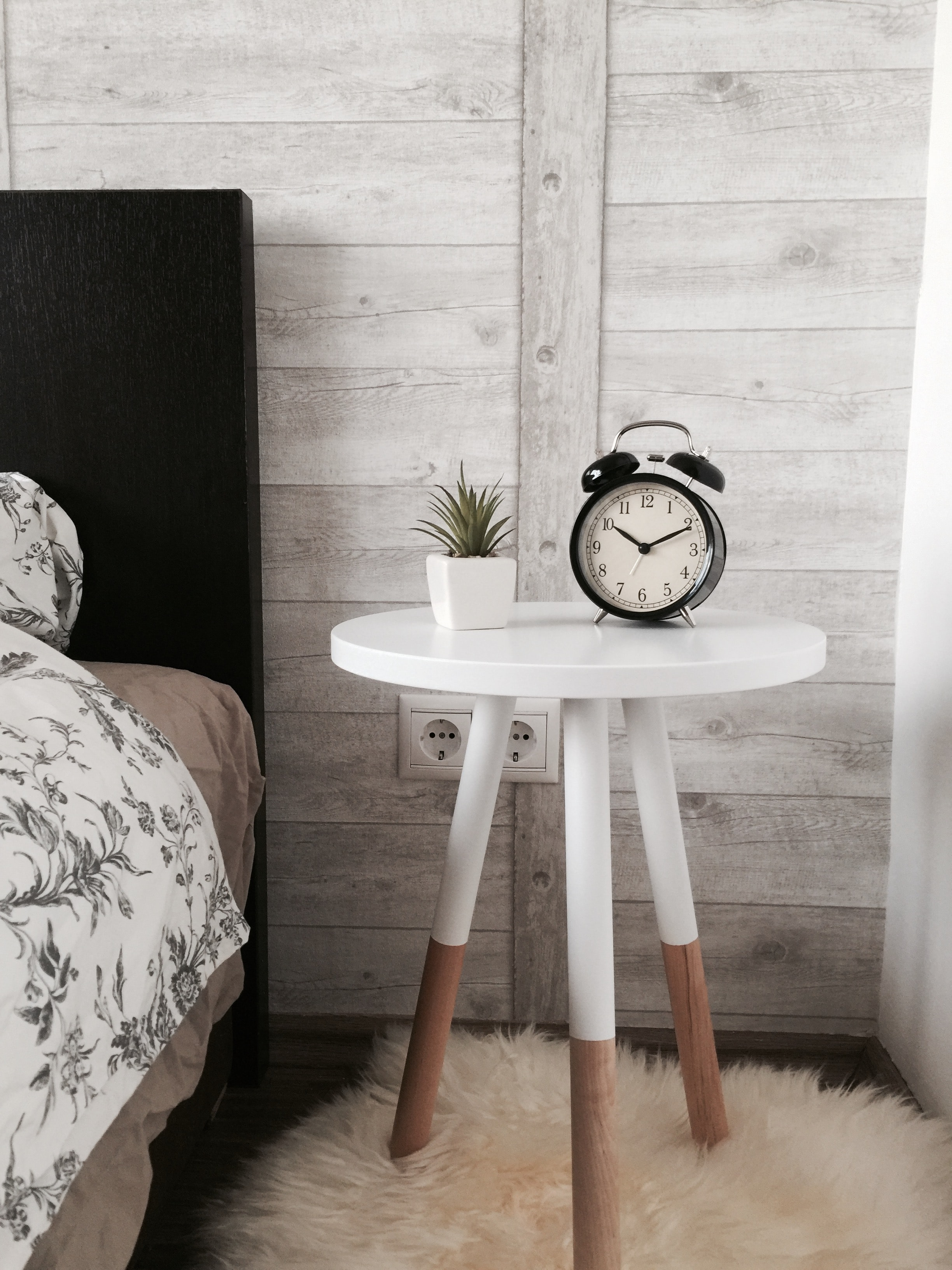 black alarm clock at 10:10 on white wooden table near table