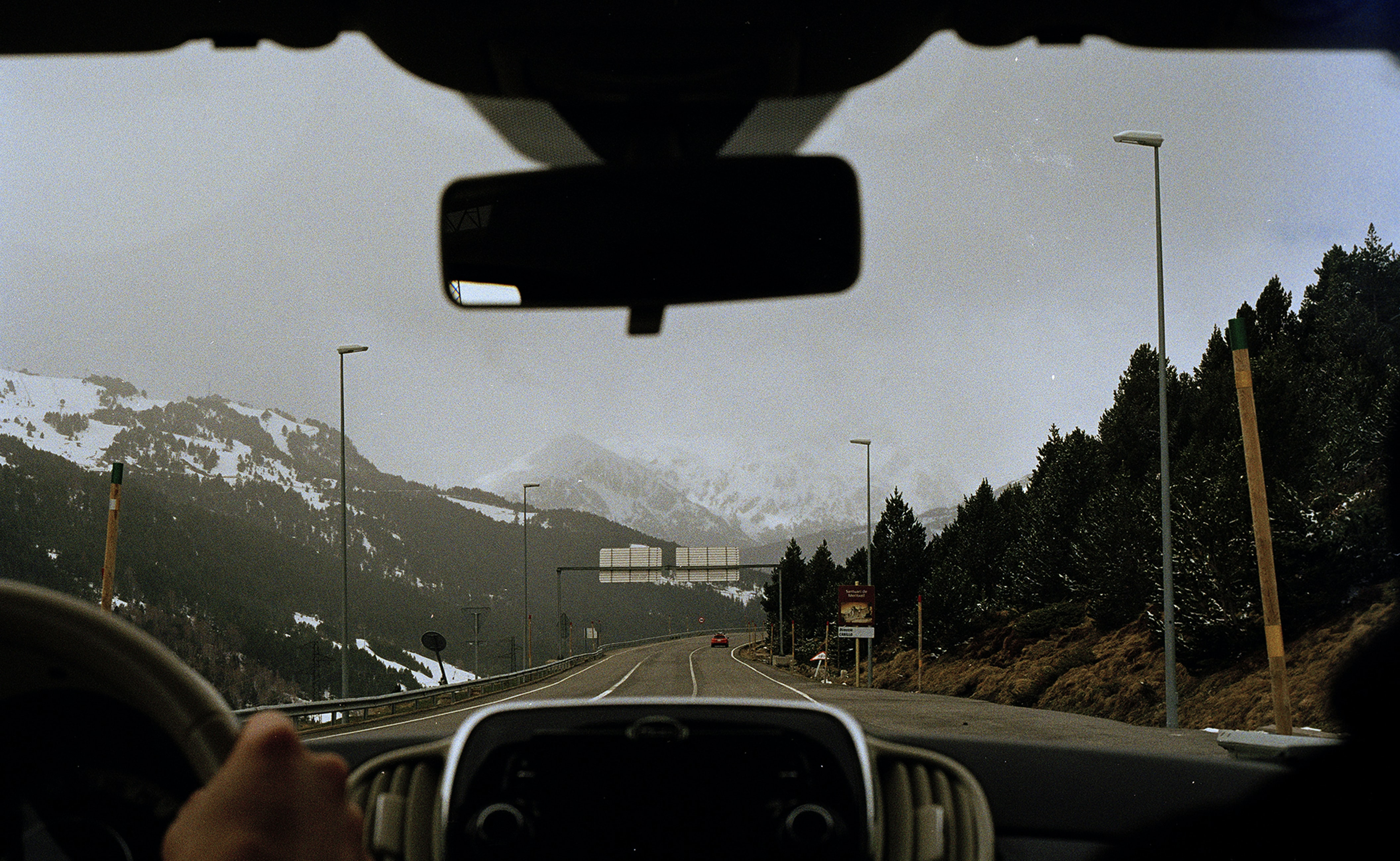A person road tripping on the highway towards the snowcapped mountains of Andorra