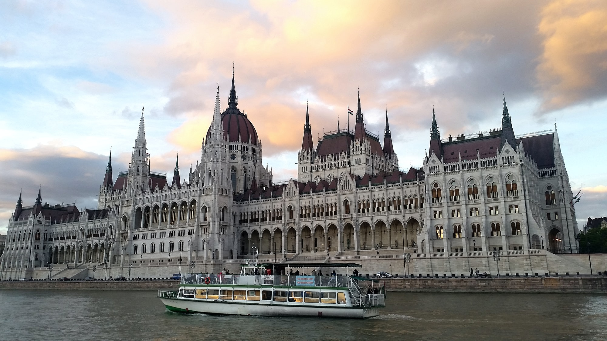 Budapest Parliament seen from a Danube boat cruise on sunset.
