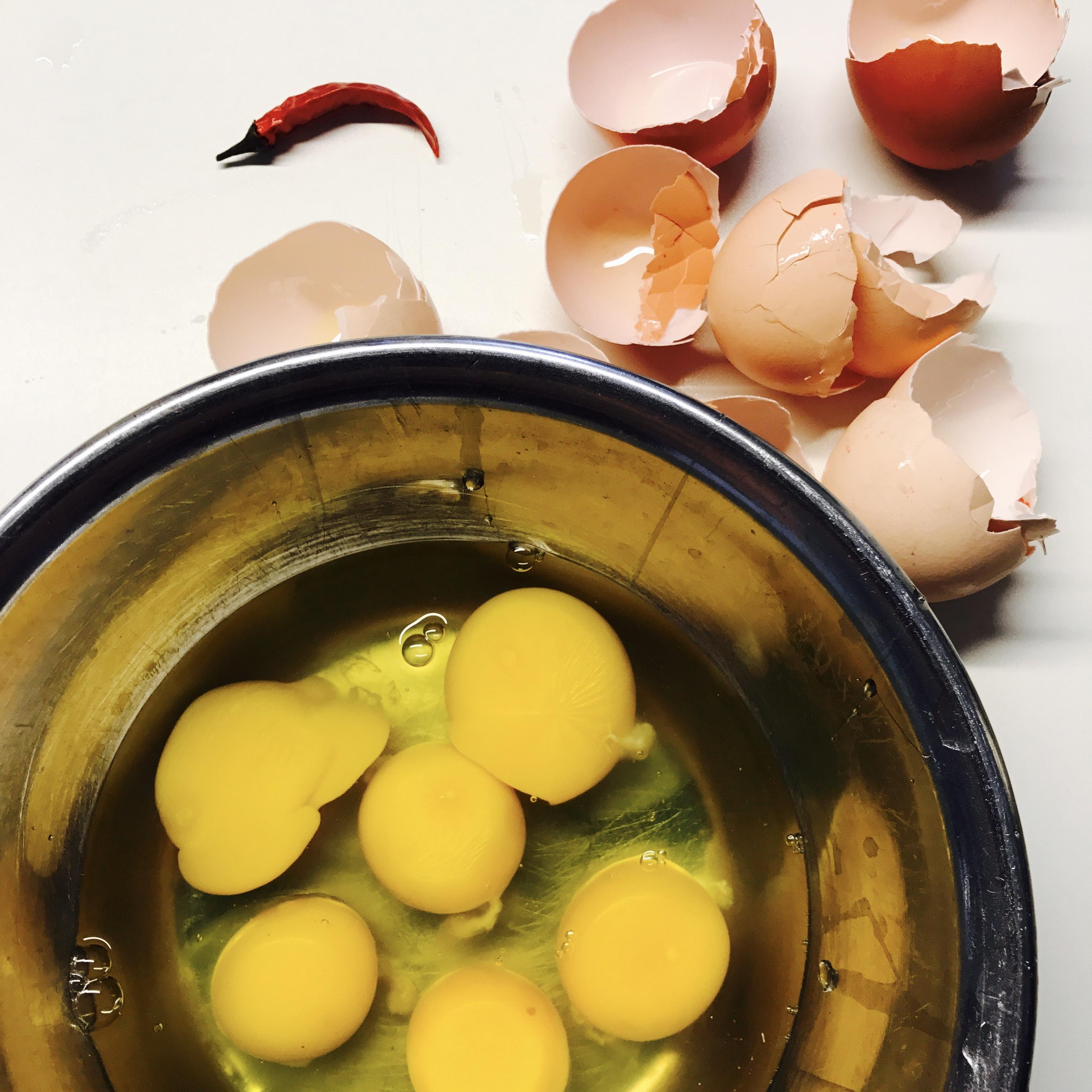 cracked eggs beside round blue bowl