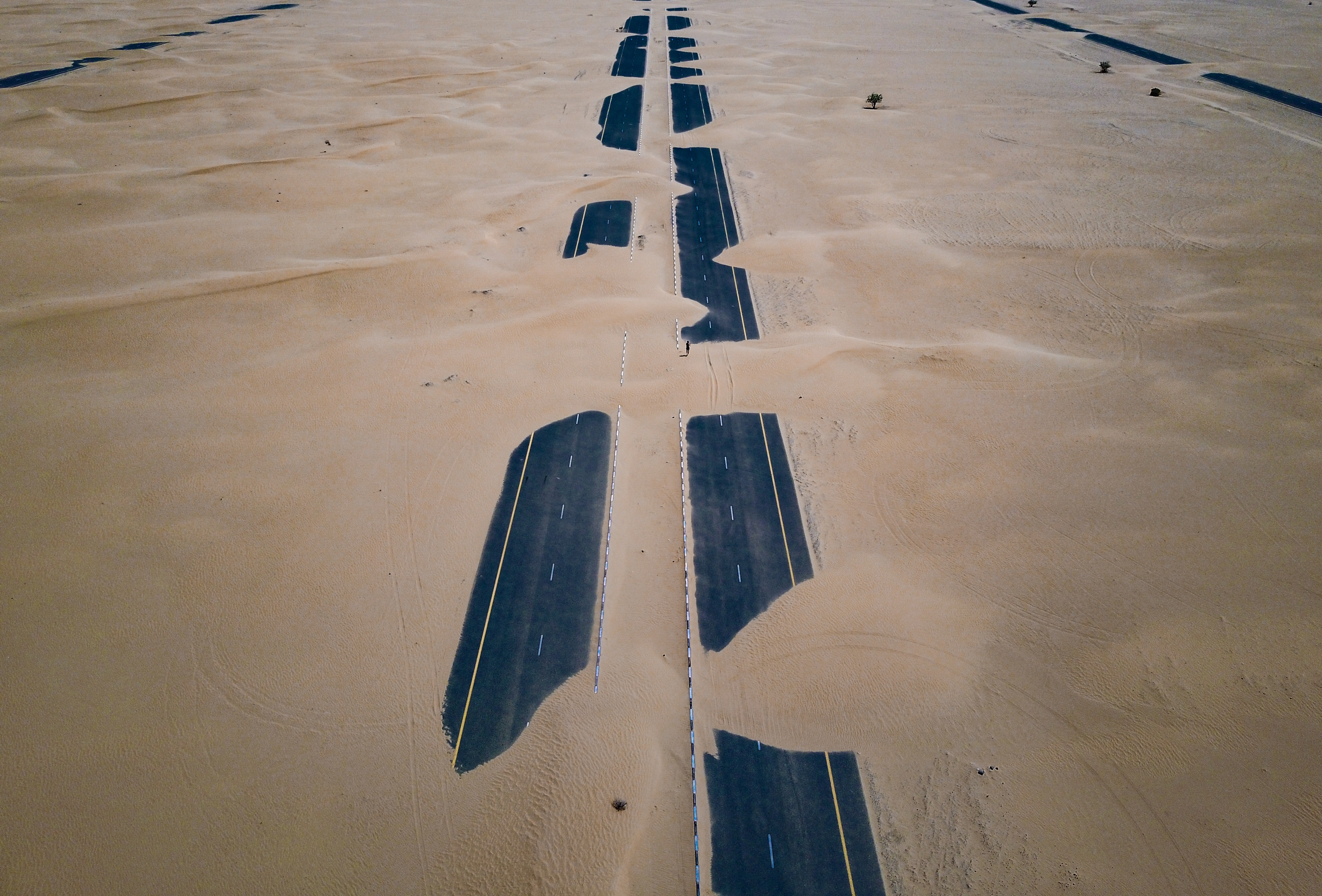 A two-lane road in Dubai covered in desert sand