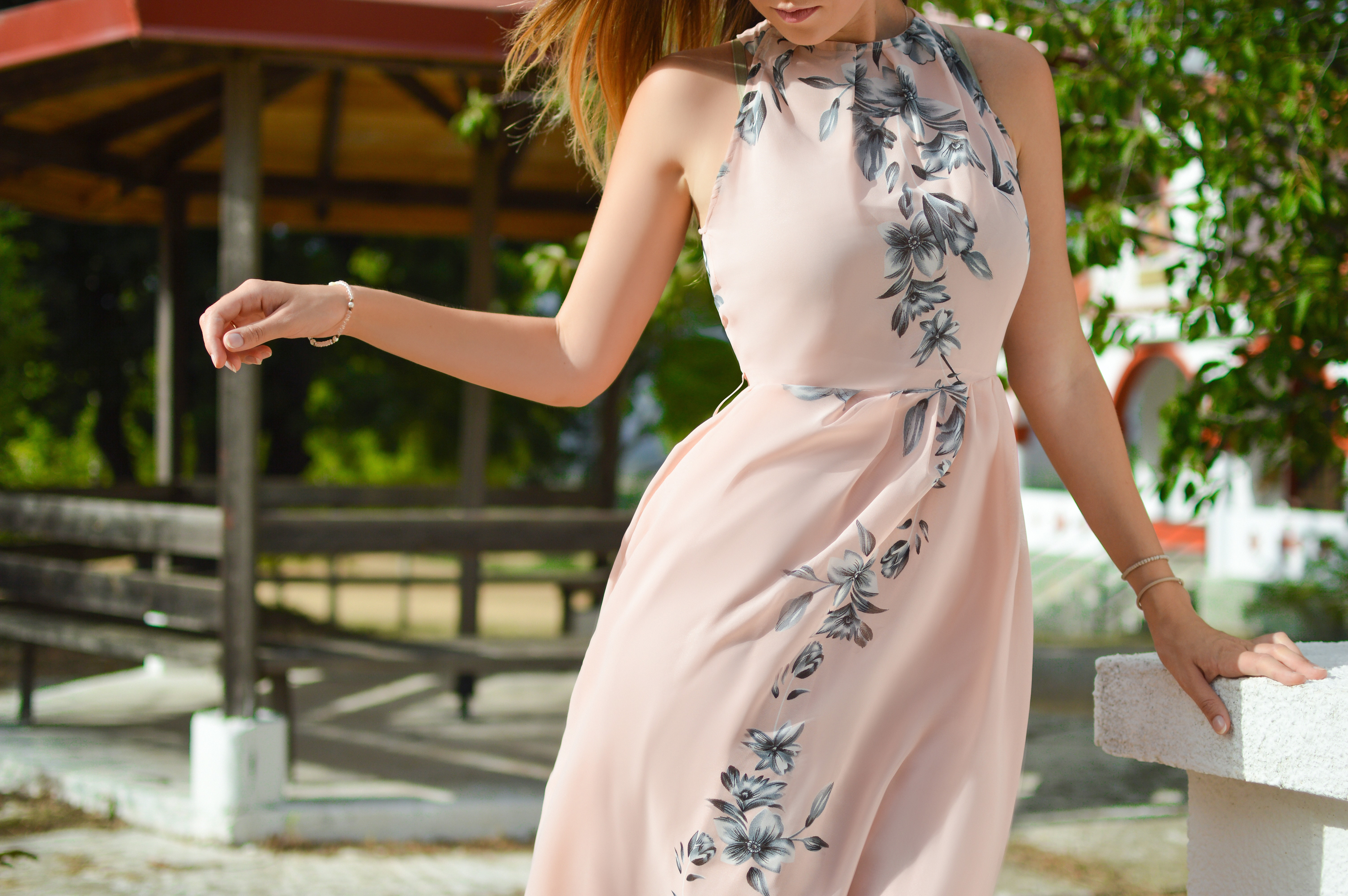 Woman in a flowy floral dress leans with windblown hair