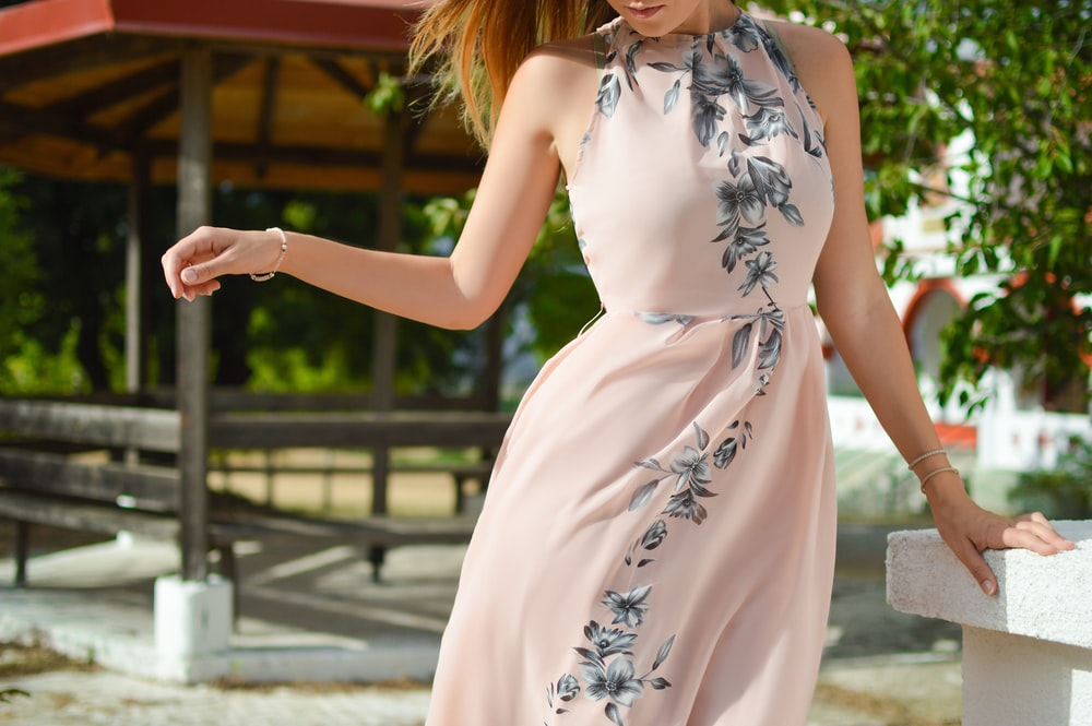 woman wearing pink, black, and white floral halter-top dress