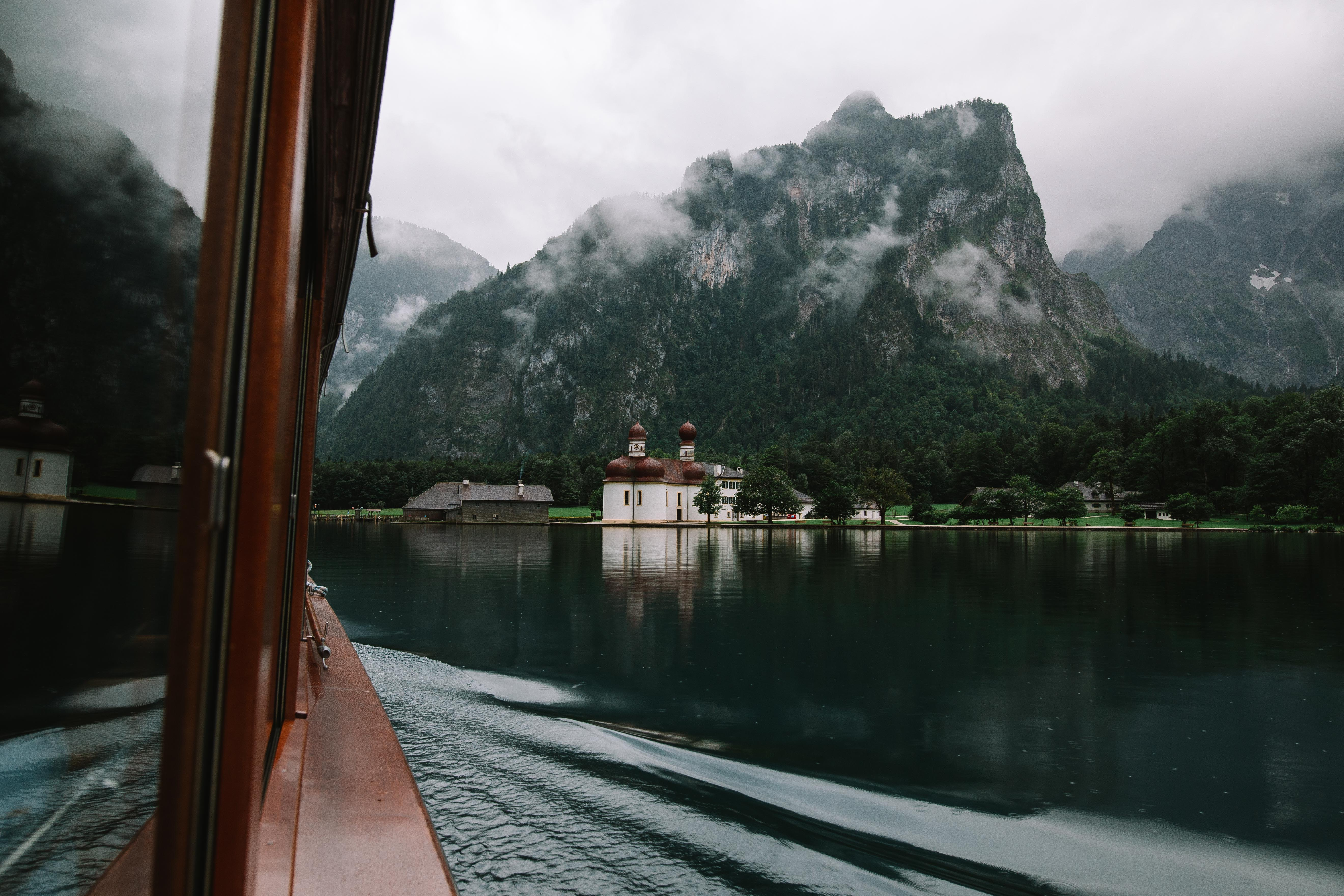 brown wooden boat on body of water in front of mountain photo