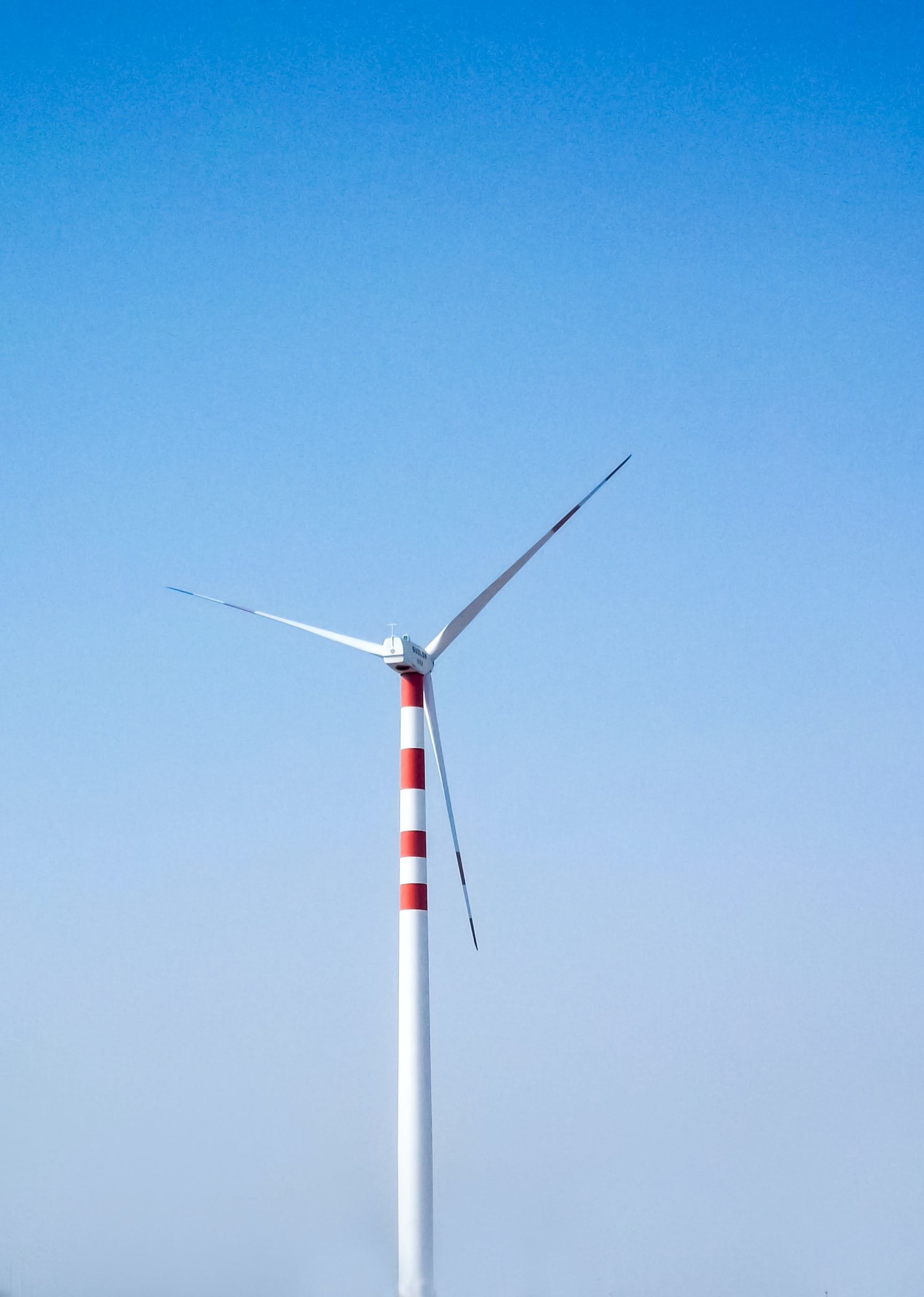 Lone wind turbine against a clear blue sky