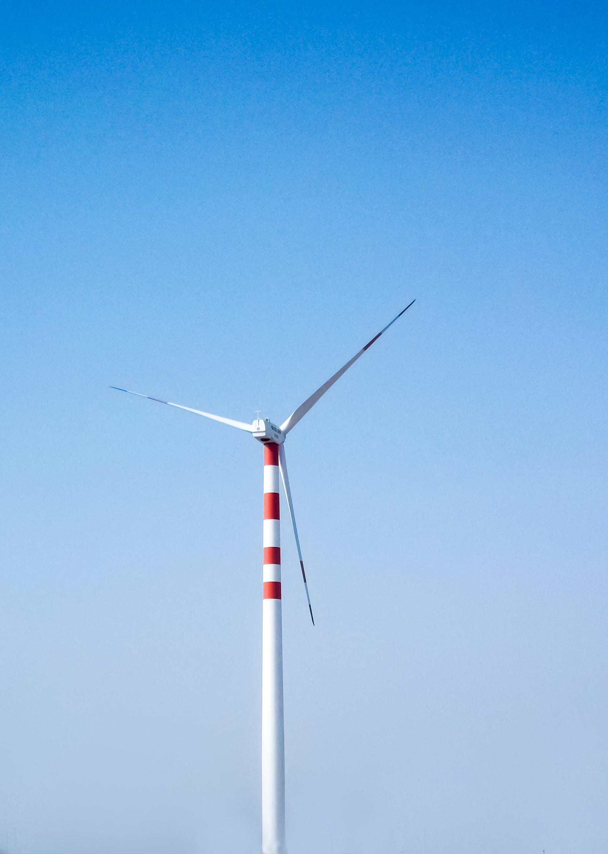 Lone wind turbine against a clear blue sky