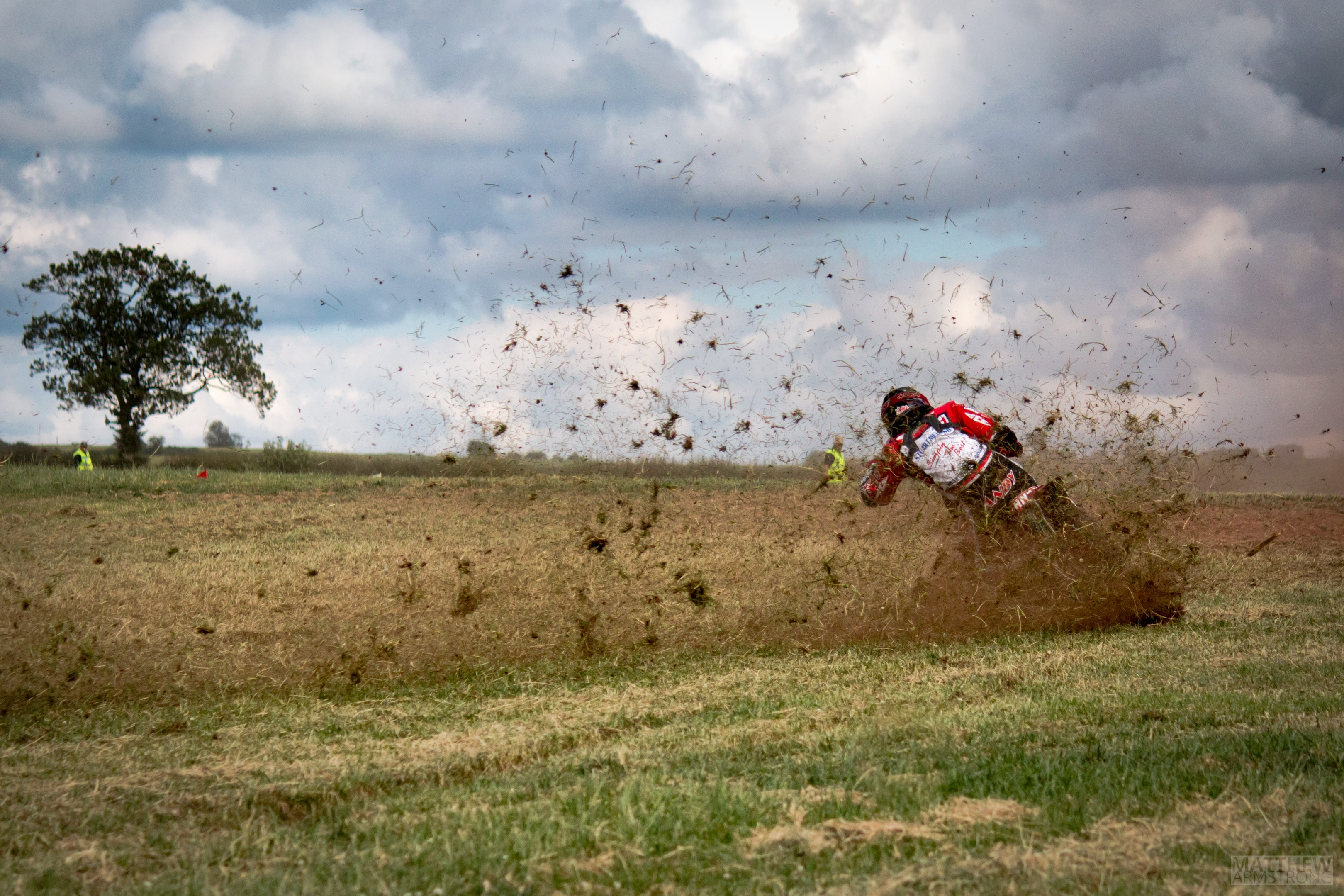man riding motorcycle drifting on green field with mud at daytime