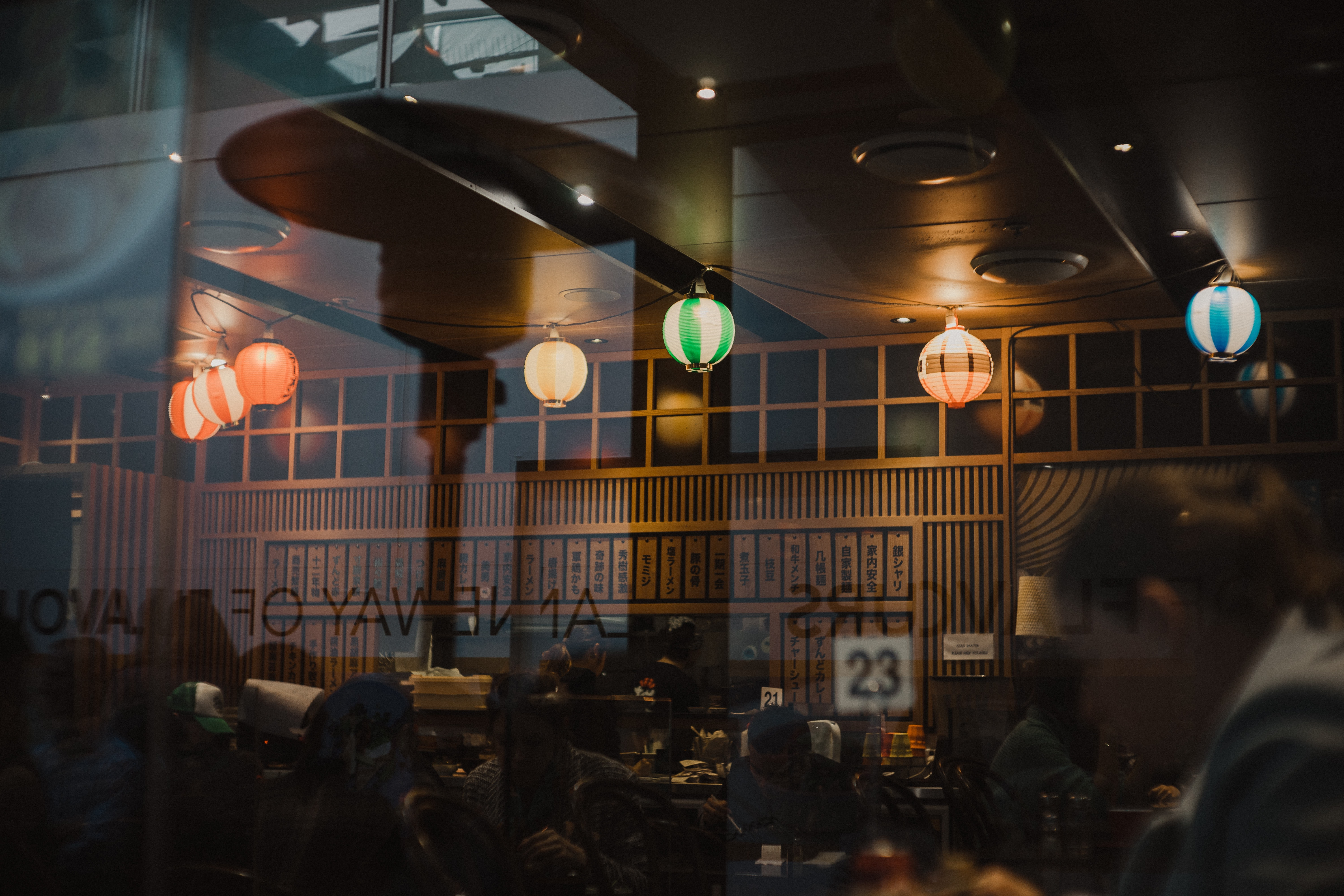 Lamps are reflected in the window of a restaurant with lanterns on the ceiling and wooden panels inside