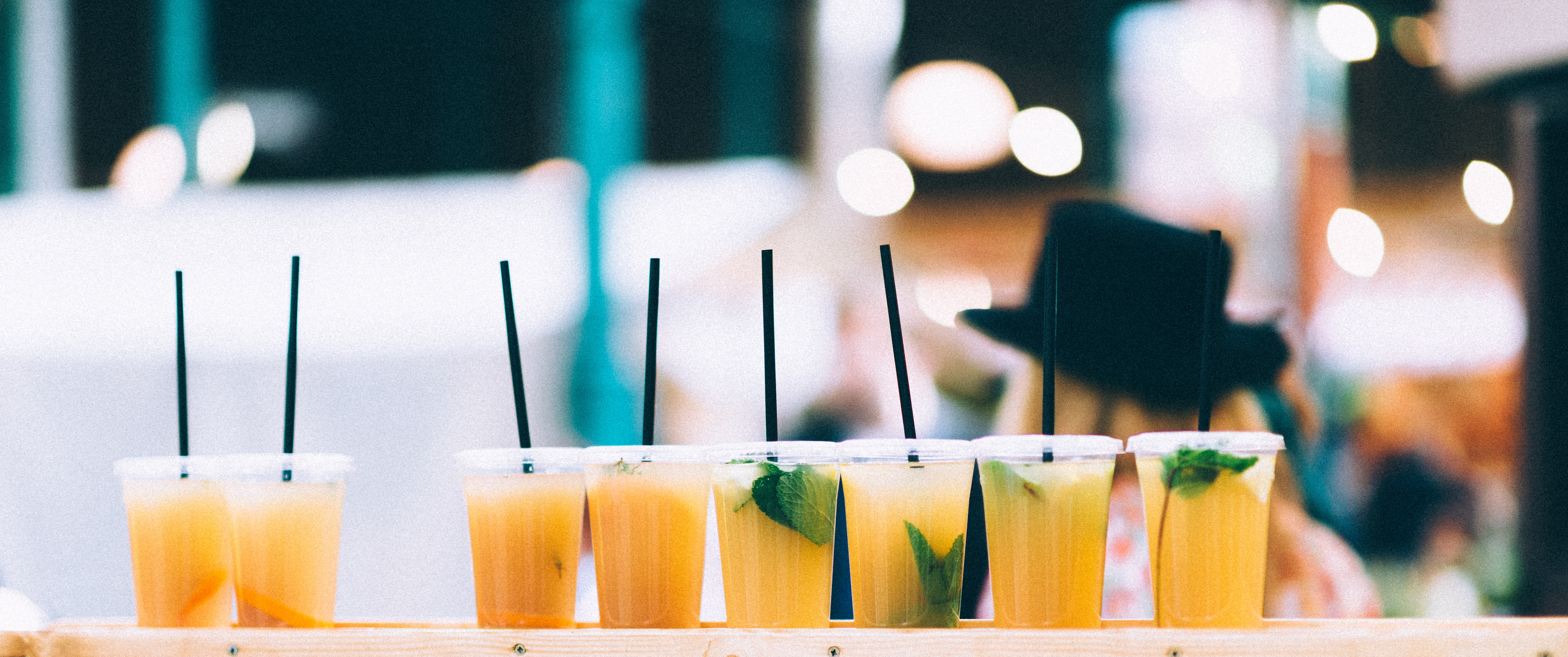 Orange cocktails with mint leaves and straws arranged in a row