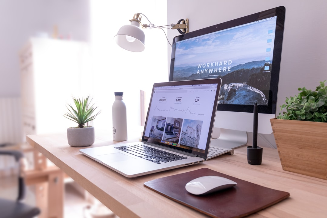 A MacBook and an iMac on a neat desk in a bright room