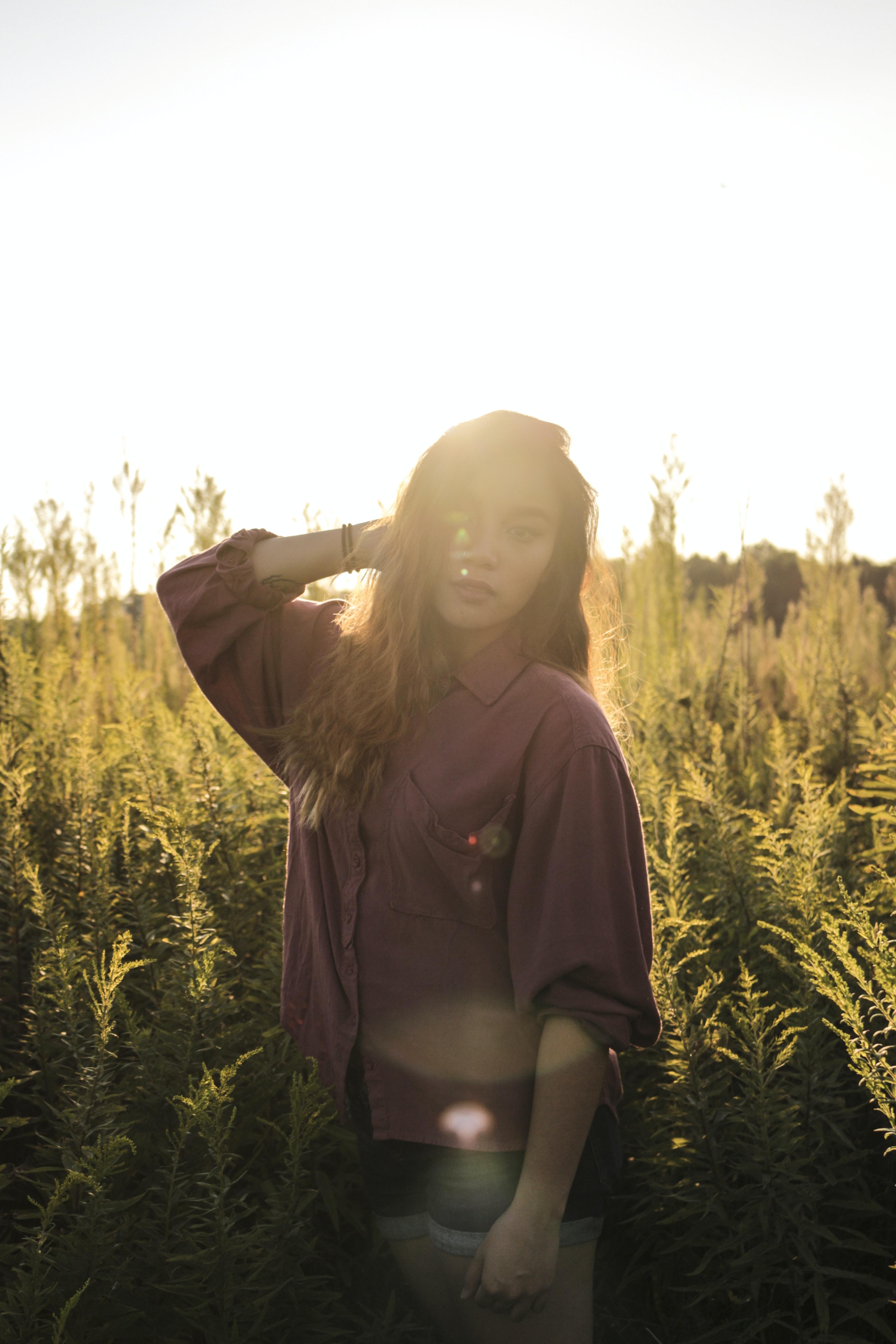 woman standing near green grass field wearing brown button-up long-sleeved dress shirt