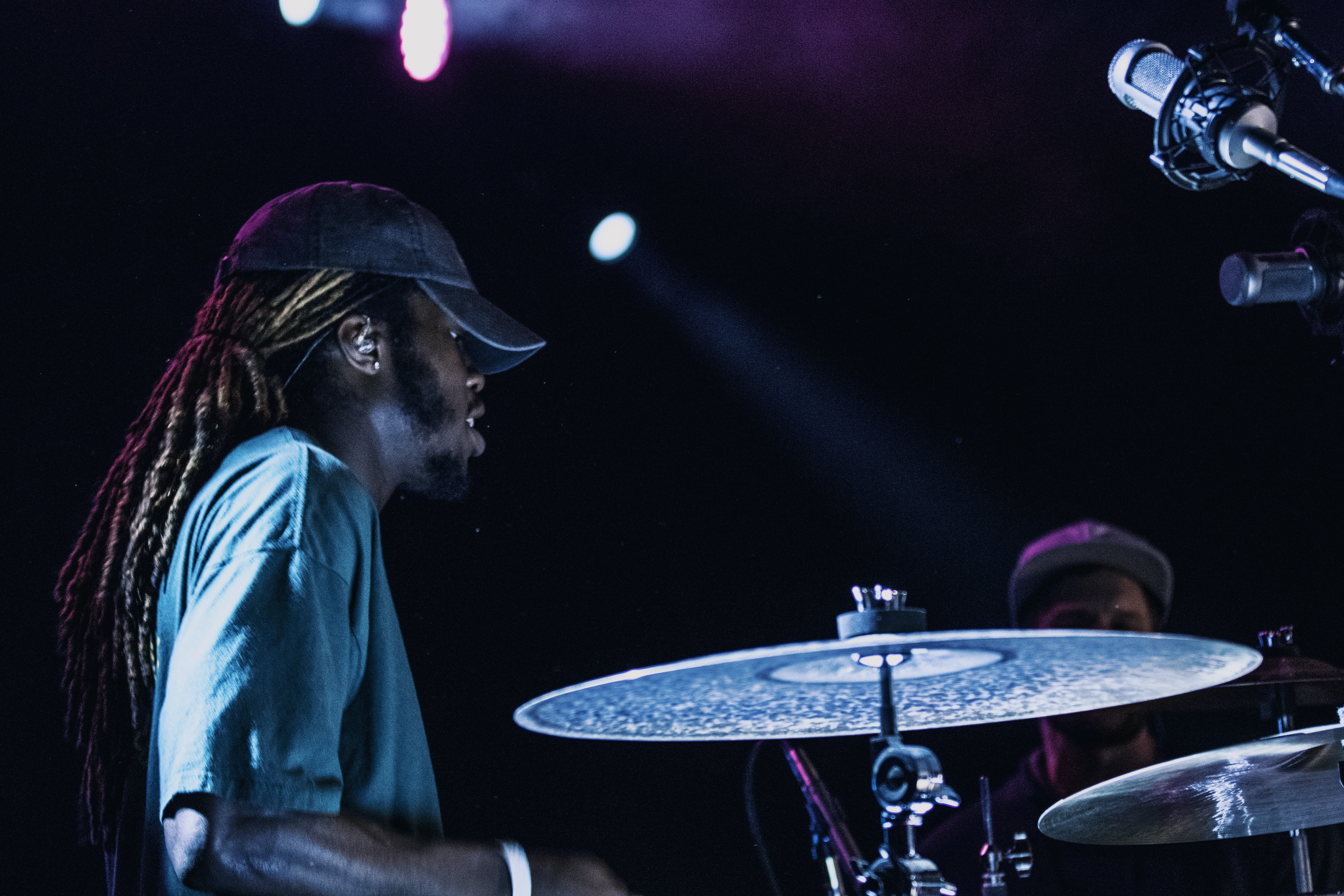man playing drums beside man wearing gray fitted cap