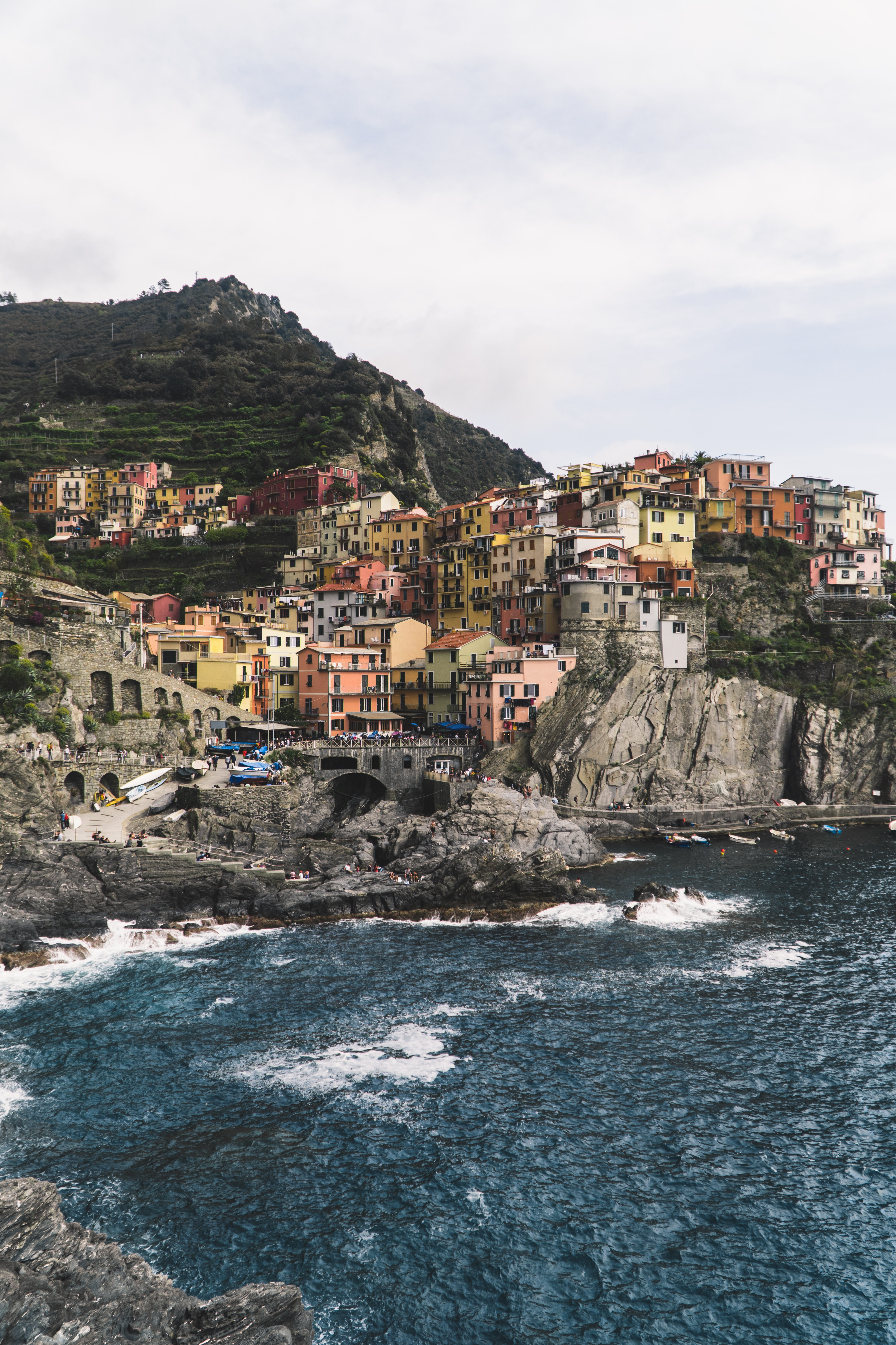 photography of assorted-color building near mountain beside seashore during daytime