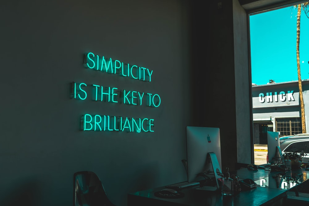 "A blue light sign on a black wall that reads ""Simplicity is the key to brilliance."""