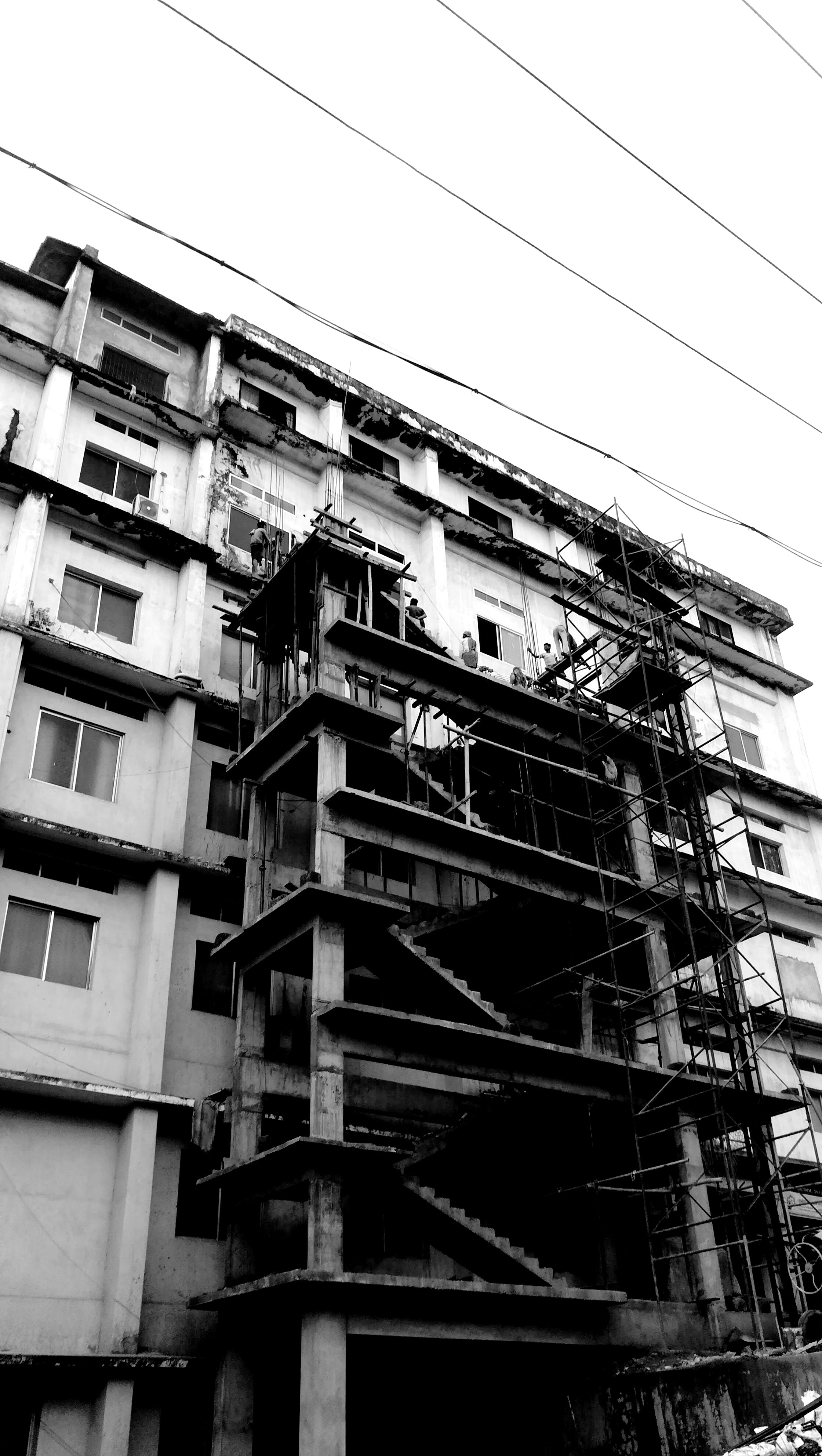 Black and white photo of apartment building with fire escape and stairs