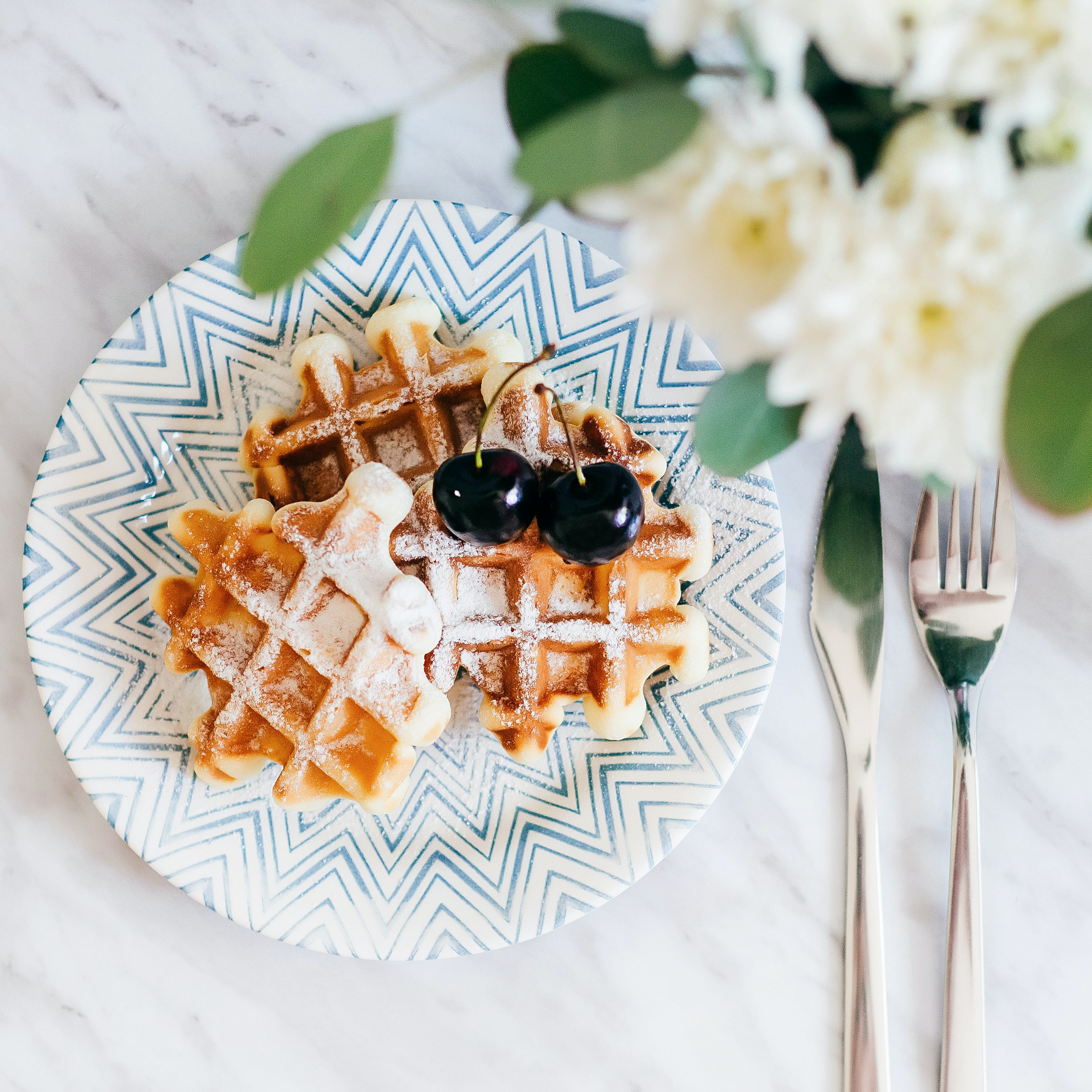 3 waffles on saucer with 2 cherry fruits beside fork and bread knife