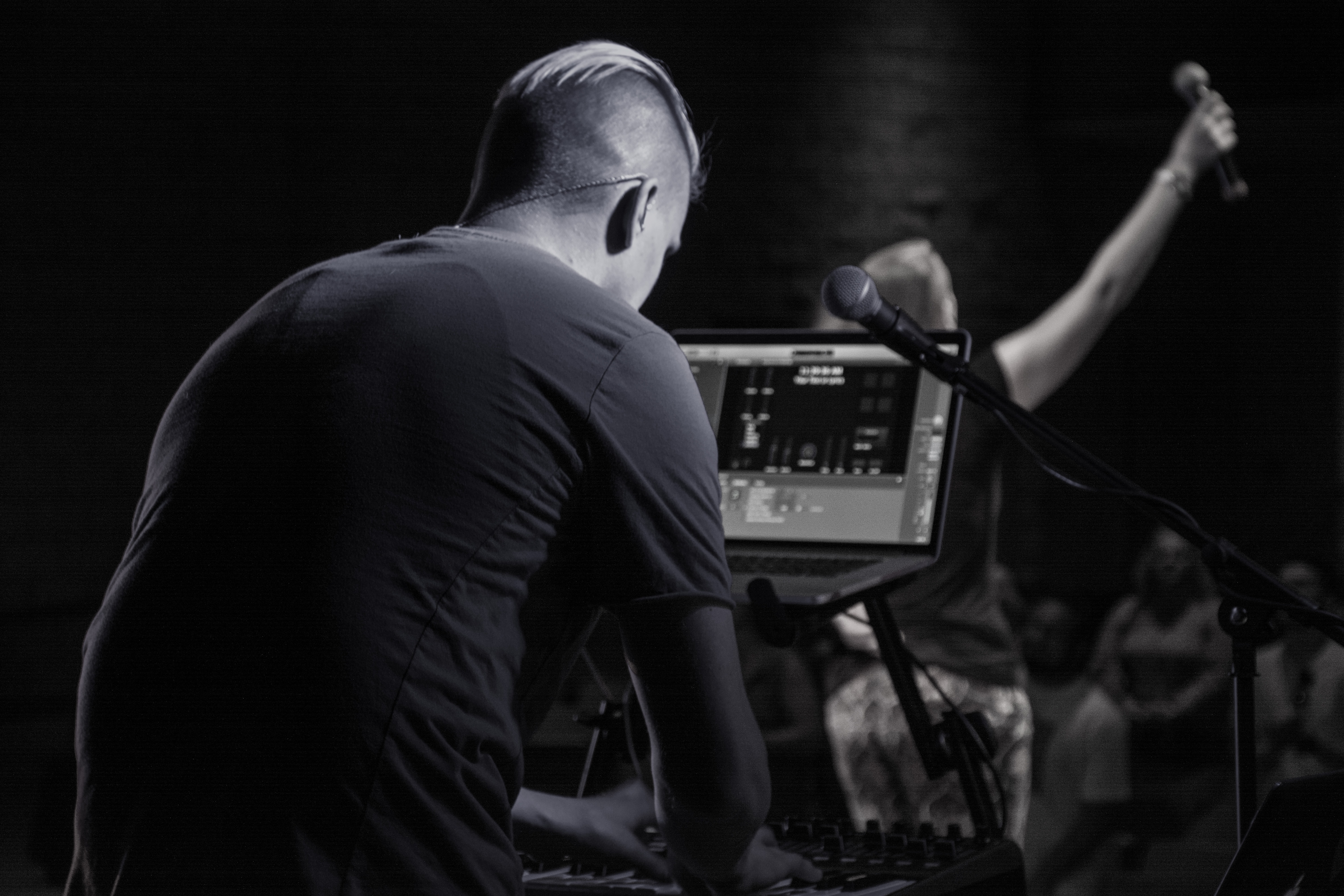 Electronic musicians perform a show using their laptop for a crowd