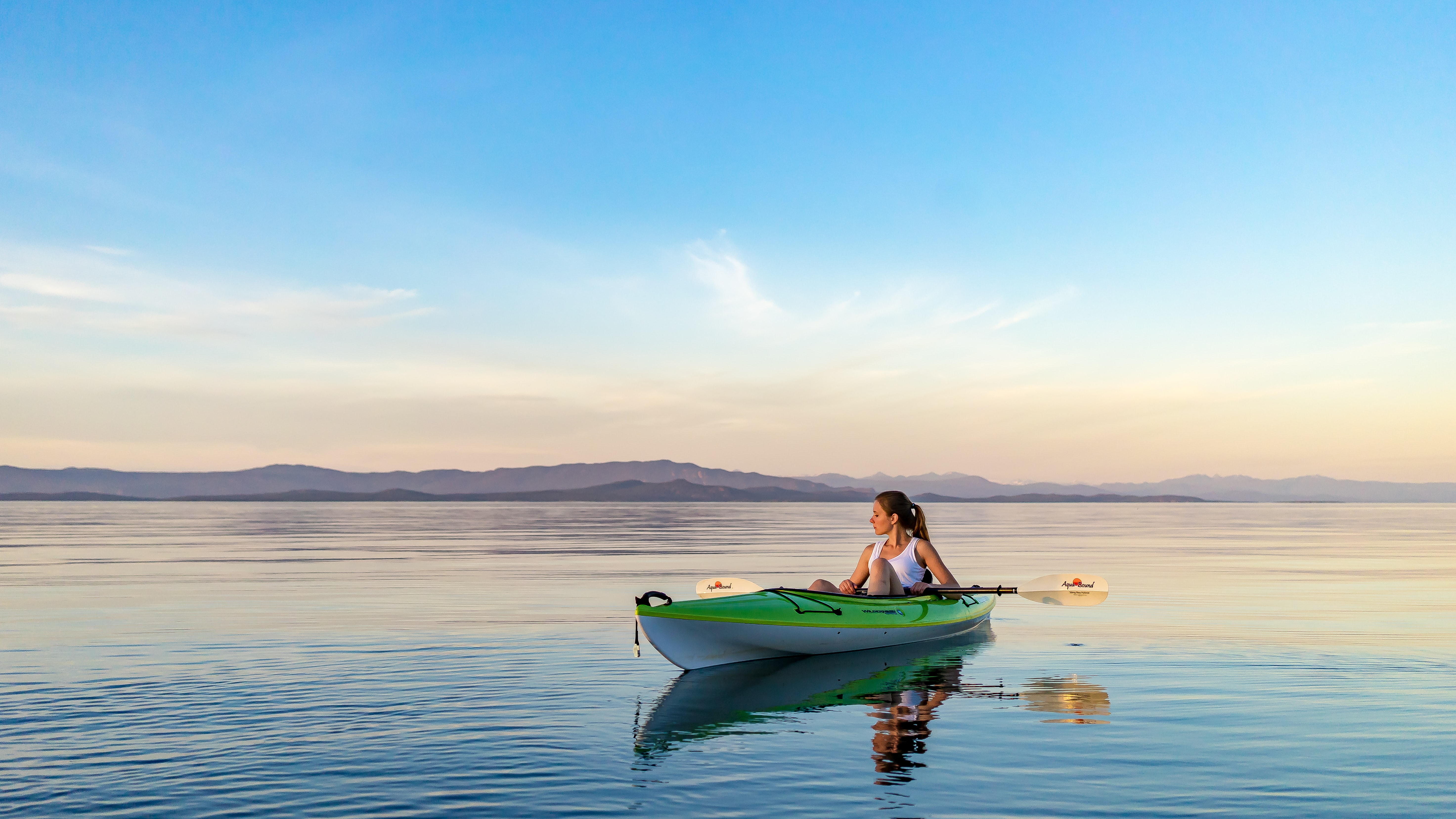 Woman in a kayak boat on a calm water at Qualicum Beach