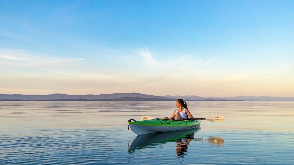 woman on green and white kayak holding yellow oar under white clouds and blue sky