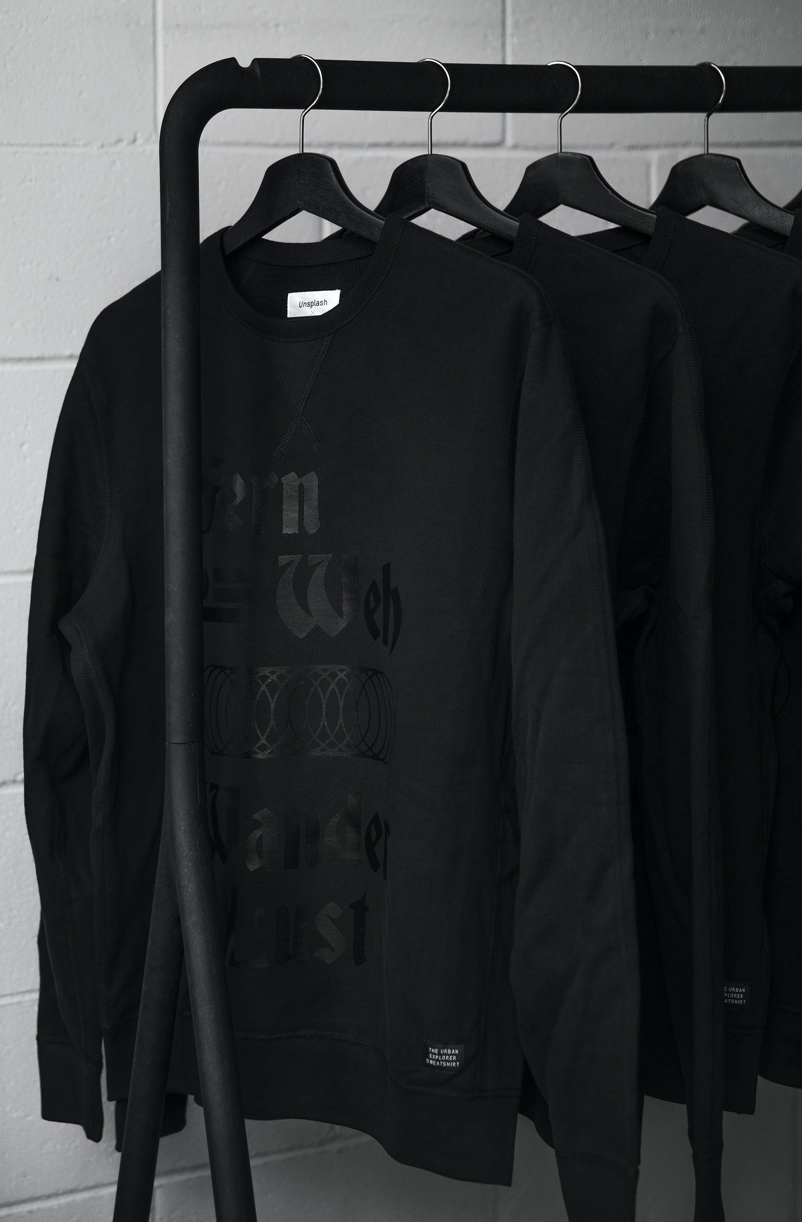 Black sweatshirts hang from black hangs on a rack against a white brick wall