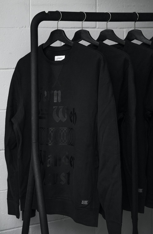 black sweatshirts on plastic hangers