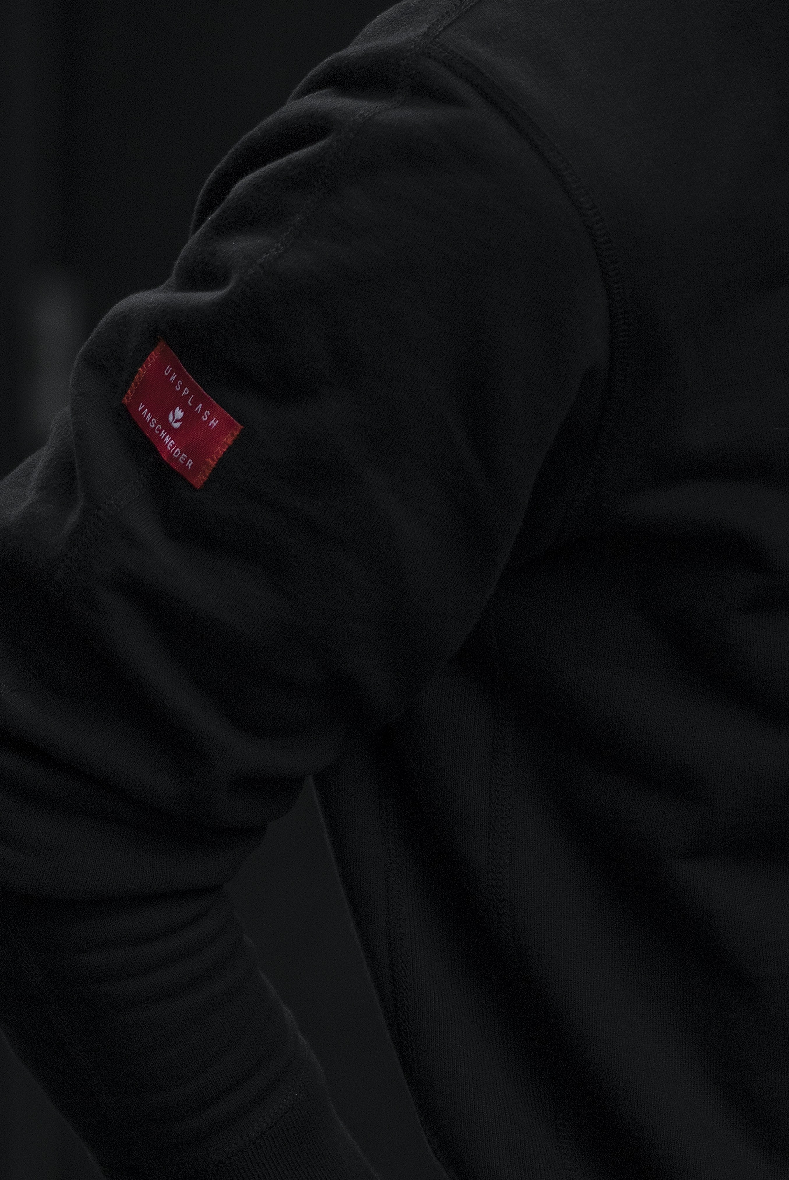 A person wears a black coat with a red Unsplash tag