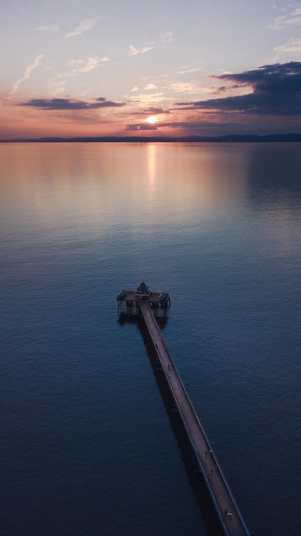 brown wooden pier dock on body of water during golden hour
