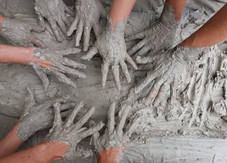 people's hand on gray mud