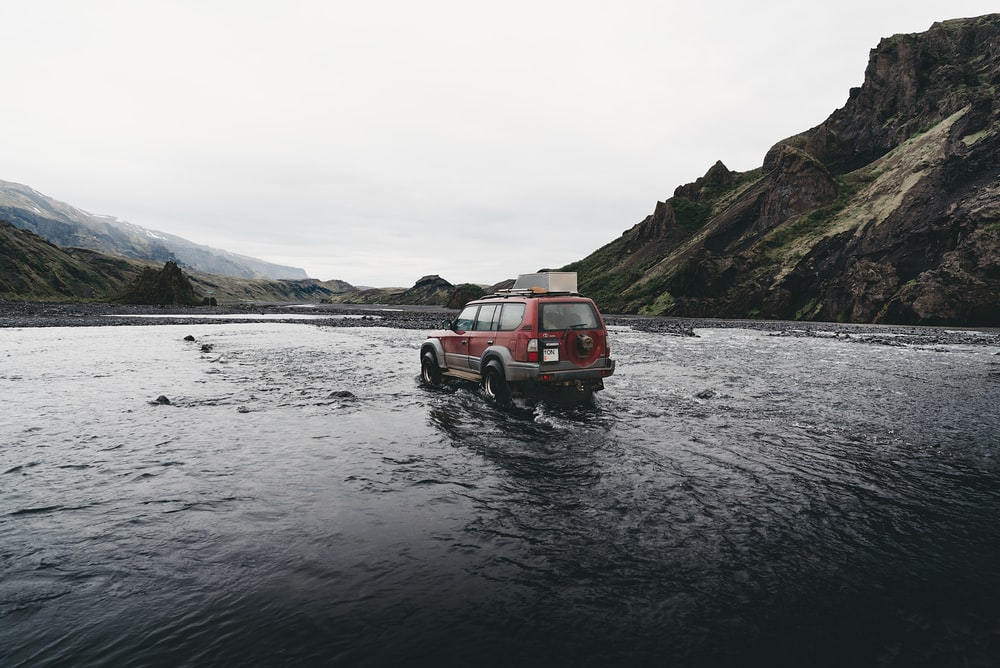 red SUV on water near mountain during daytime