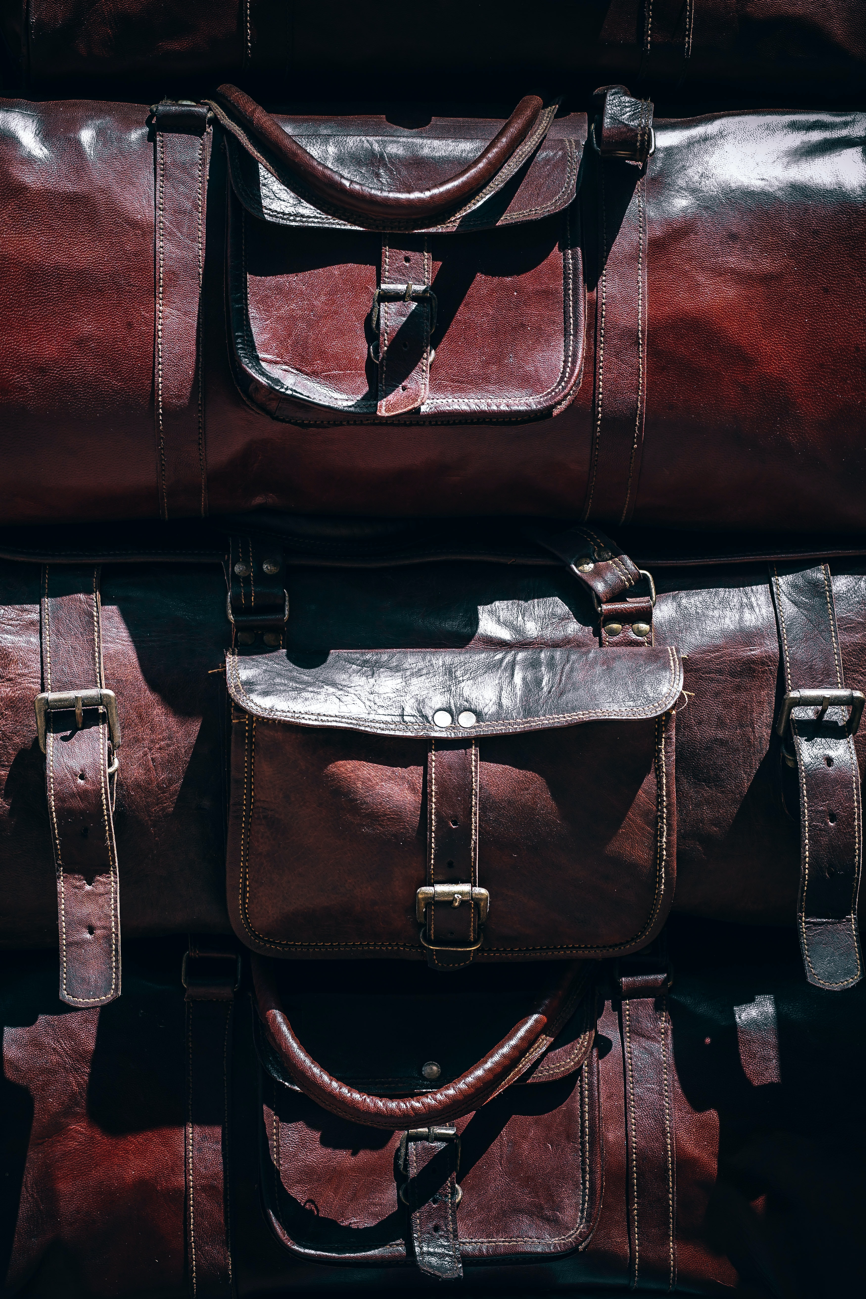 three brown leather duffel bags closeup photography