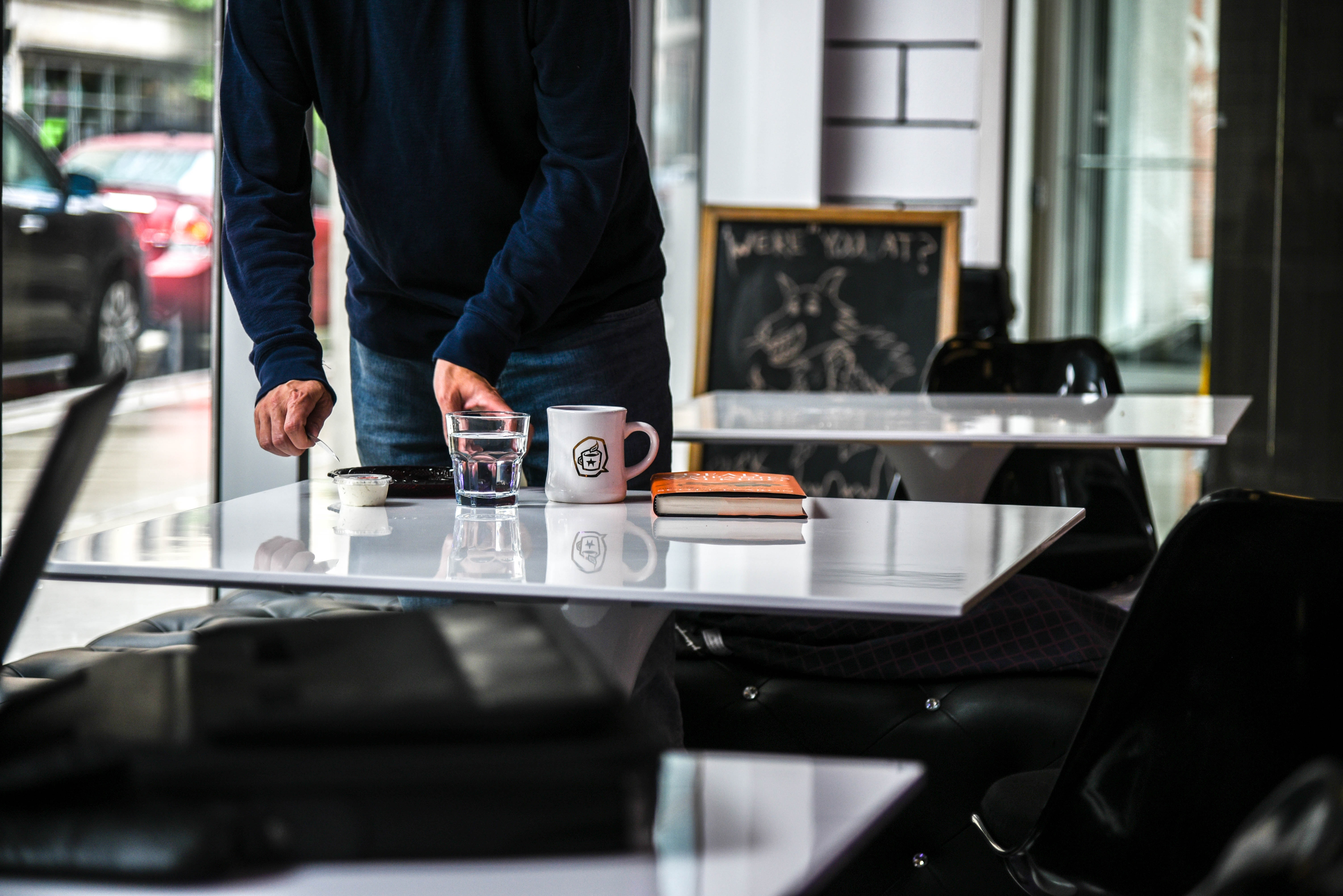standing person holding glass of water on beside table