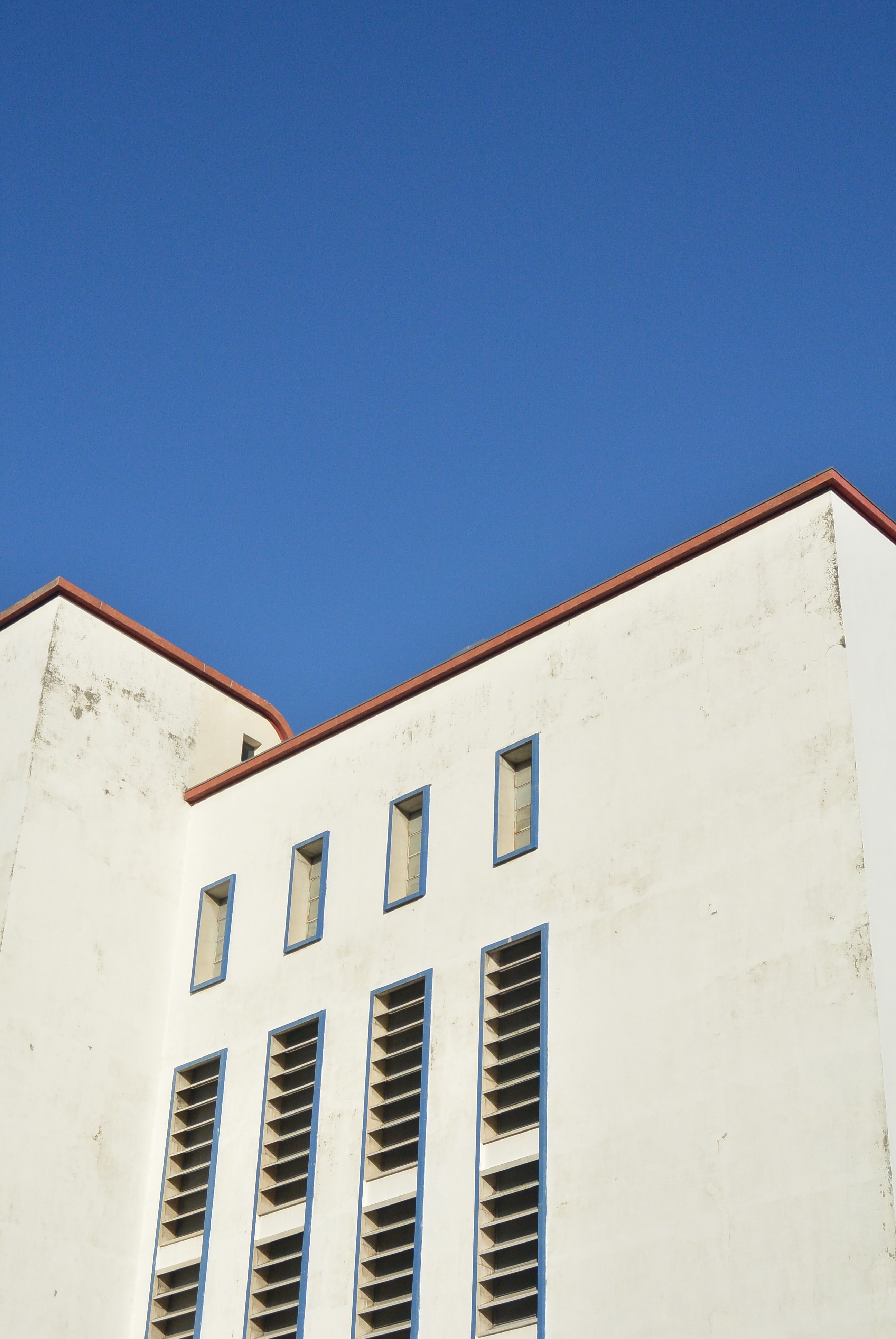 A worn-out white facade in Lisbon under a blue sky