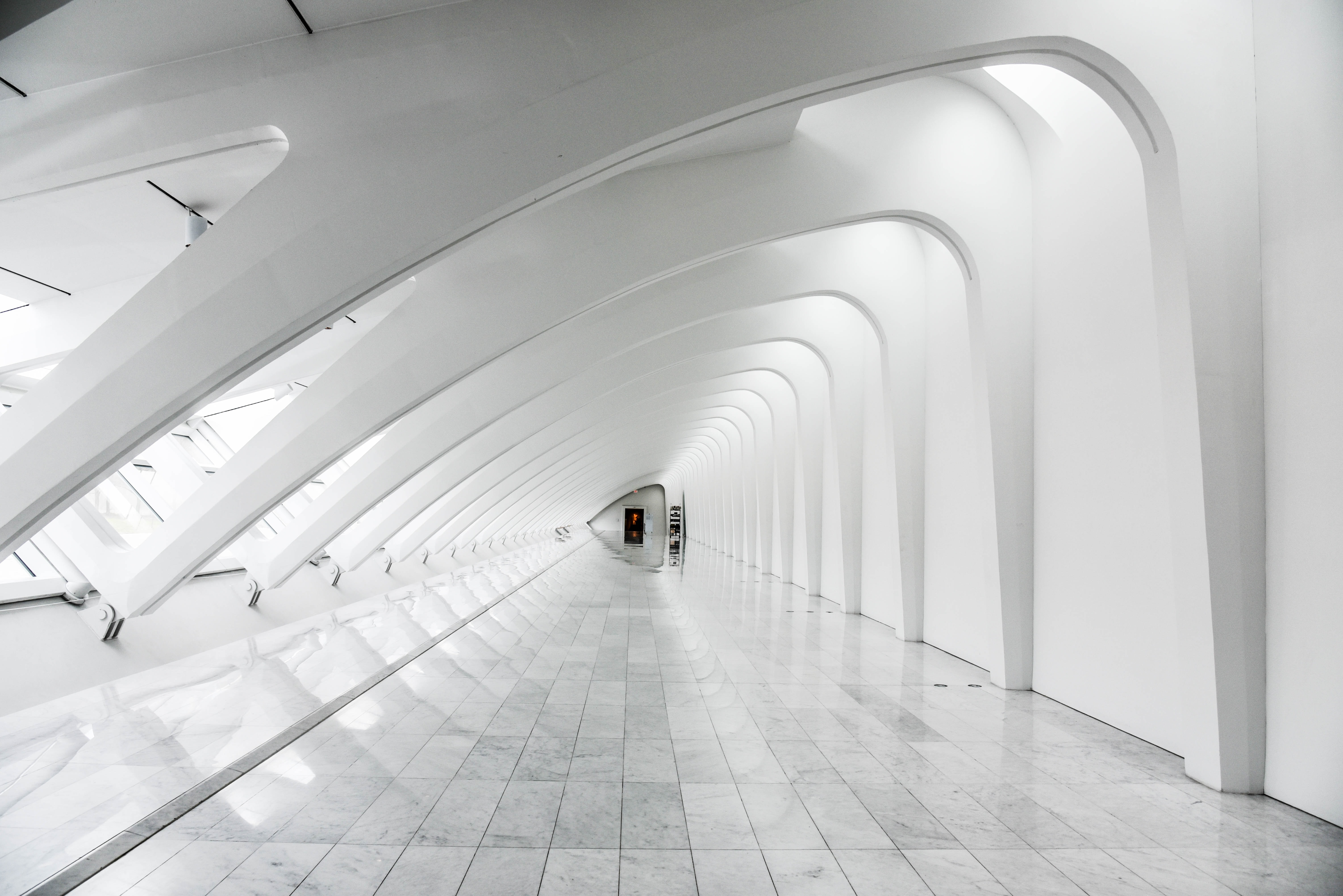 A long white corridor with a marble floor under a modern ribbed ceiling