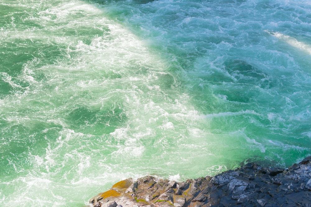 photo of body of water near gray stone